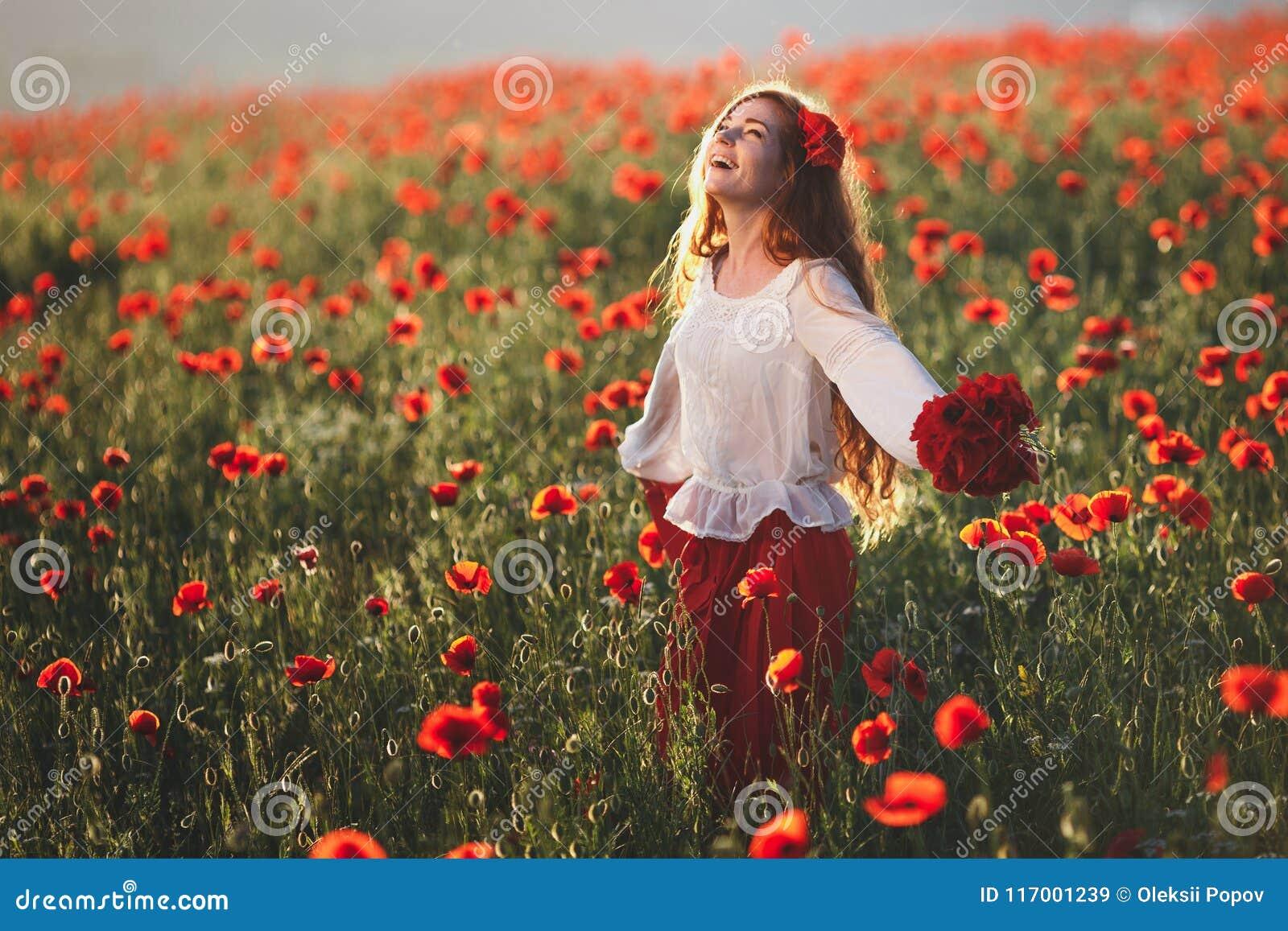 Ung härlig kvinna som går och dansar till och med ett vallmofält på solnedgången