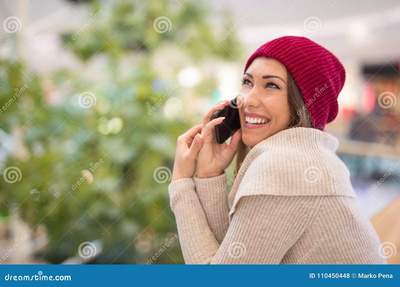 Ung härlig kvinna som talar på telefonen på gallerian