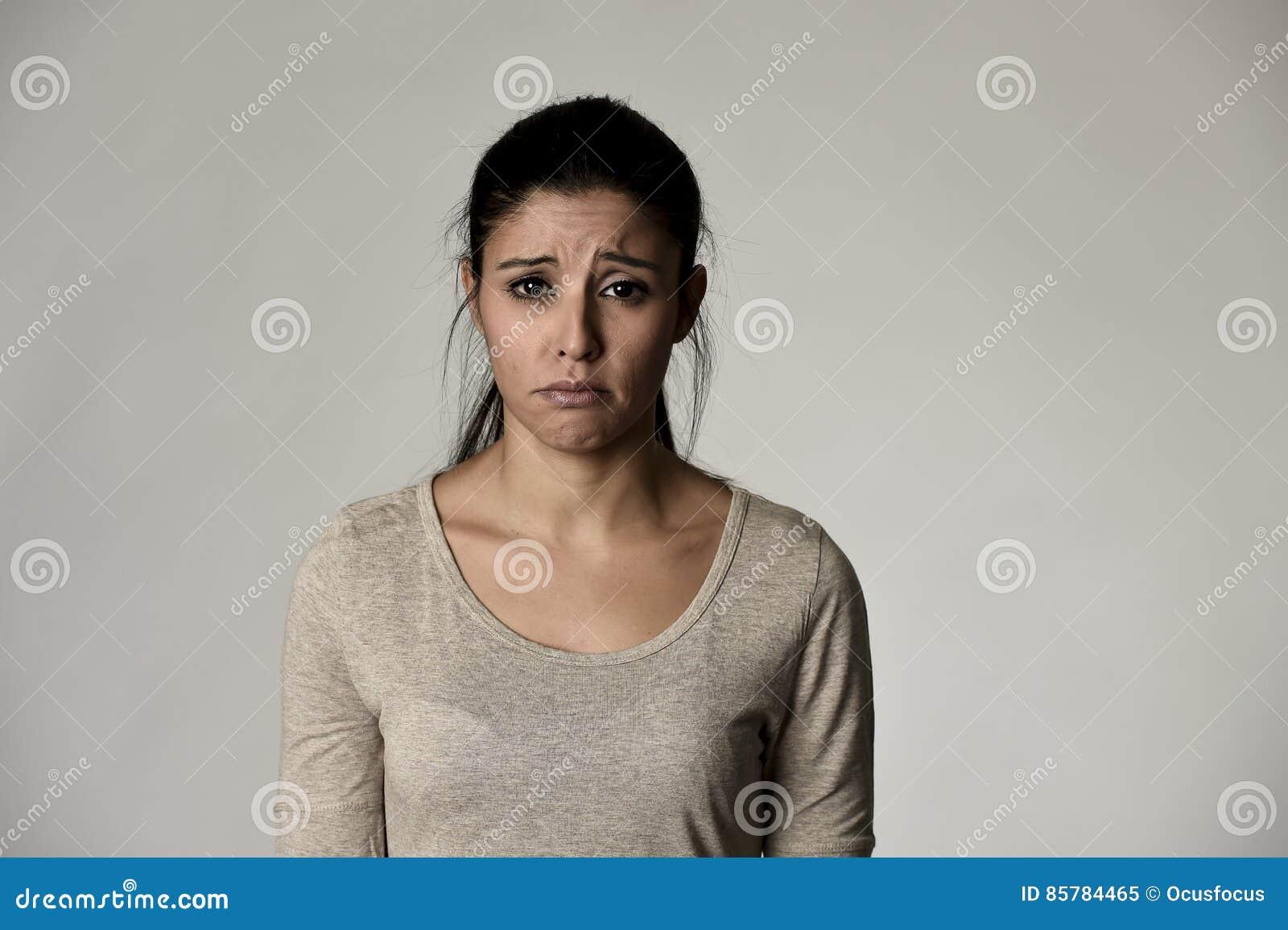 Ung härlig latinamerikansk ledsen kvinna som är allvarlig och som är bekymrad i bekymrat deprimerat ansiktsuttryck