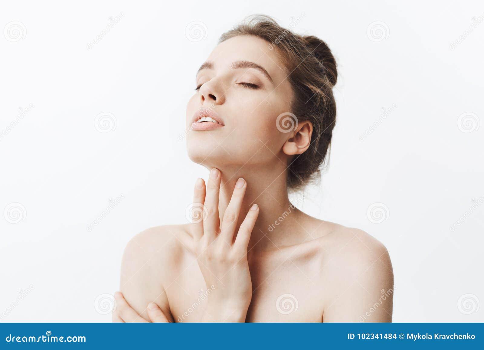 Ung härlig mörker-haired caucasian kvinna med bullefrisyren och nakna skuldror som plundrar huvudet med stängda ögon