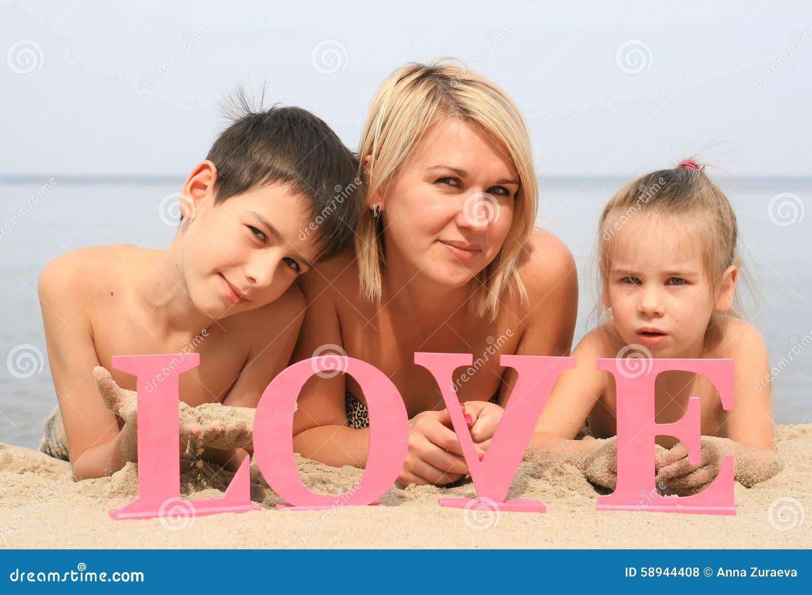 Ung härlig moder med barn som ligger på stranden med ordförälskelse