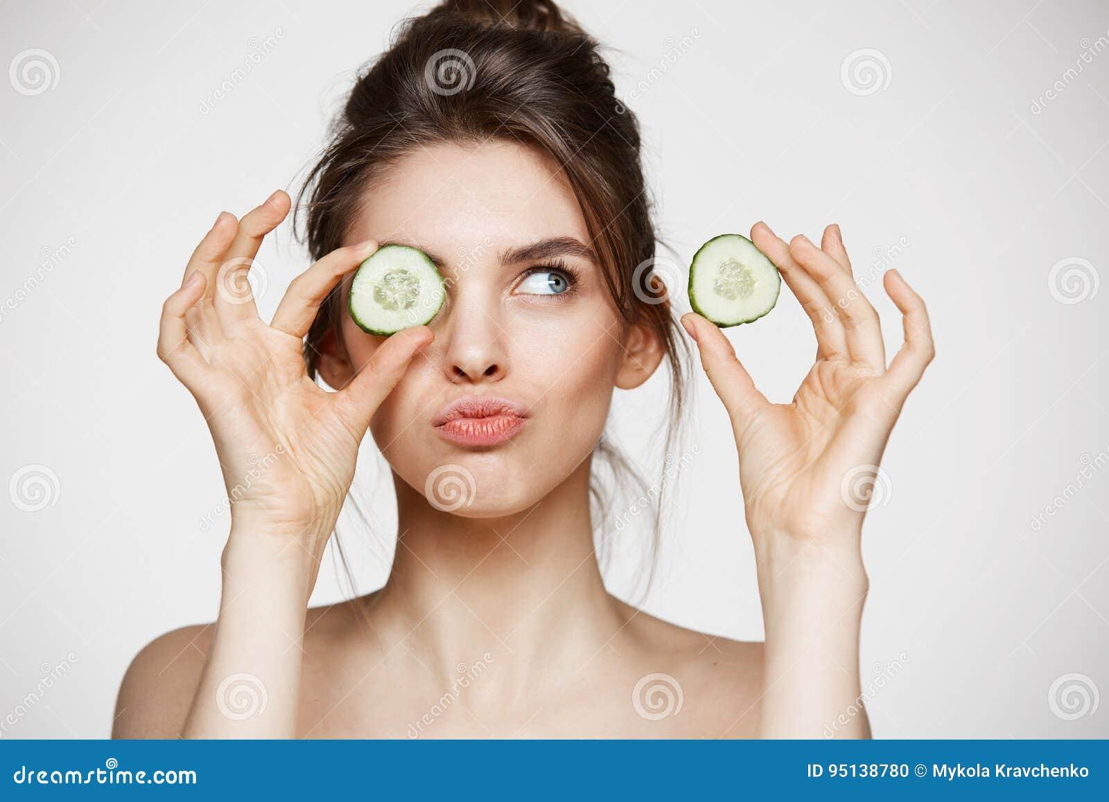 Ung härlig naken flicka som ler nederlagögat bak gurkaskiva över vit bakgrund Skönhetbrunnsort och cosmetology