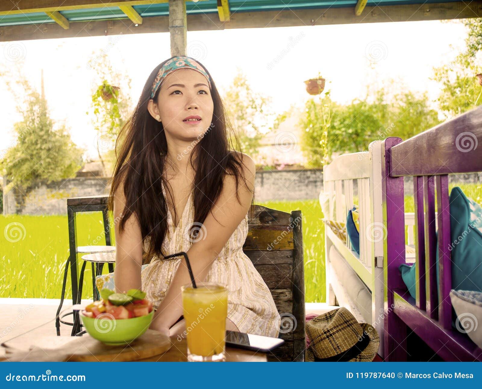 Ung härlig och lycklig asiatisk kinesisk kvinna som dricker orange fruktsaft som utomhus äter sund sallad på enjoen för coffee sh