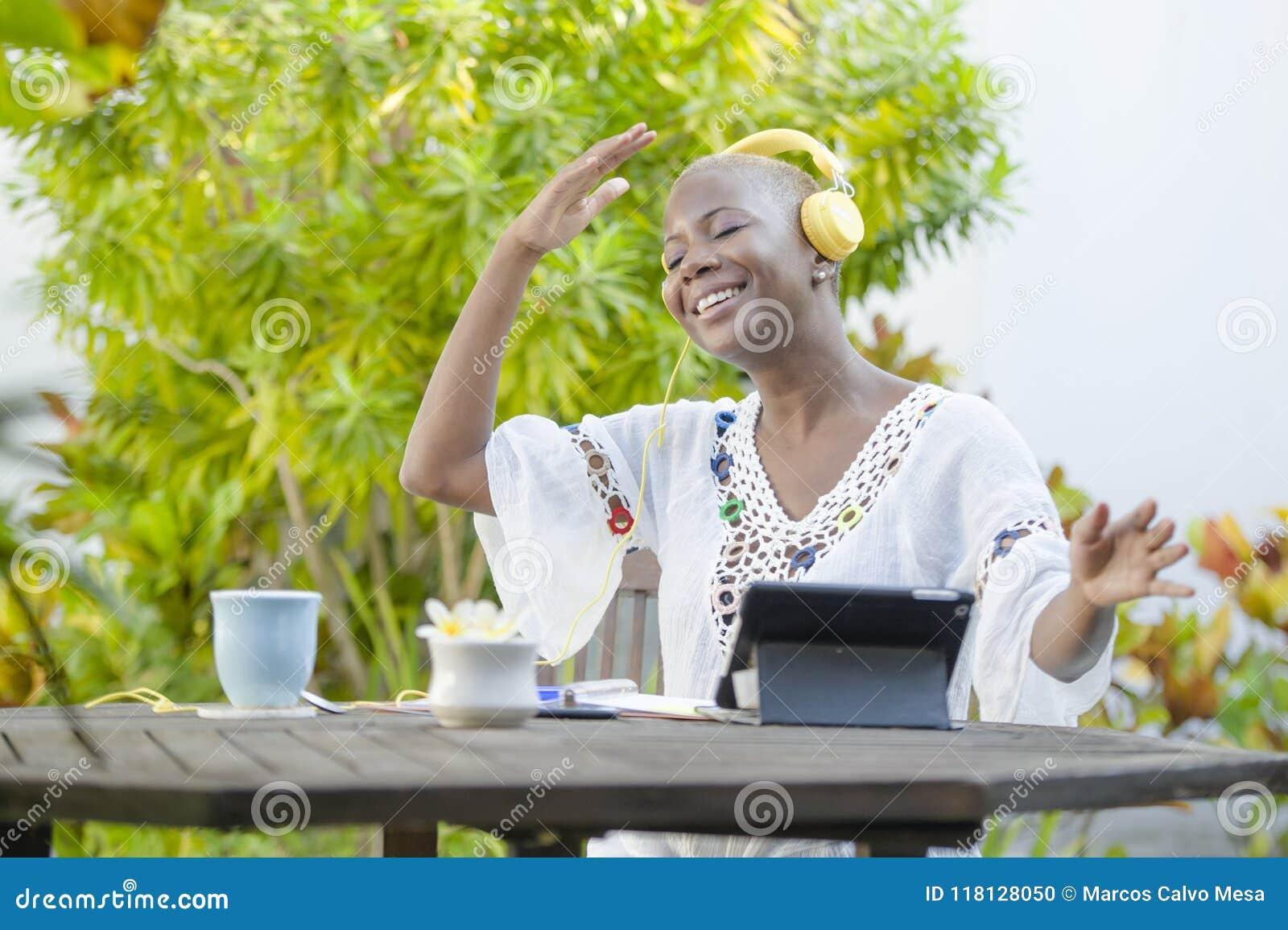 Ung härlig och lycklig svart afrikansk amerikankvinna som utomhus tycker om på kafét som arbetar med den digitala minnestavlan so