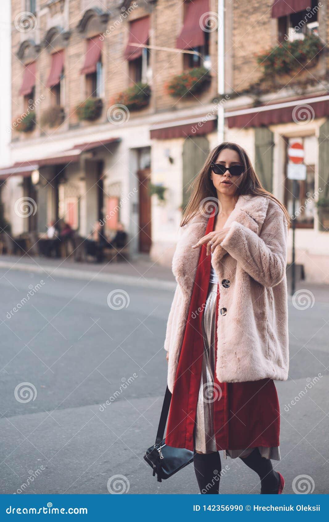 Ung härlig stilfull kvinna som går i rosa lag