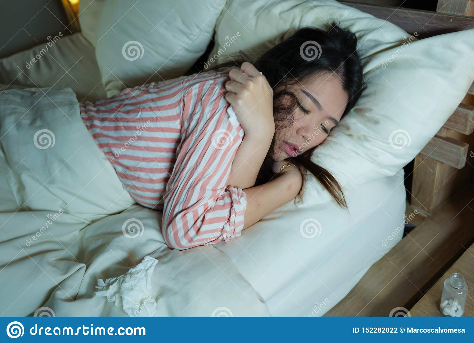 Ung härlig trött och sjuk asiatisk kinesisk kvinna som dåligt ligger på säng i pyjamas på natten med silkespapperlegitimationshan