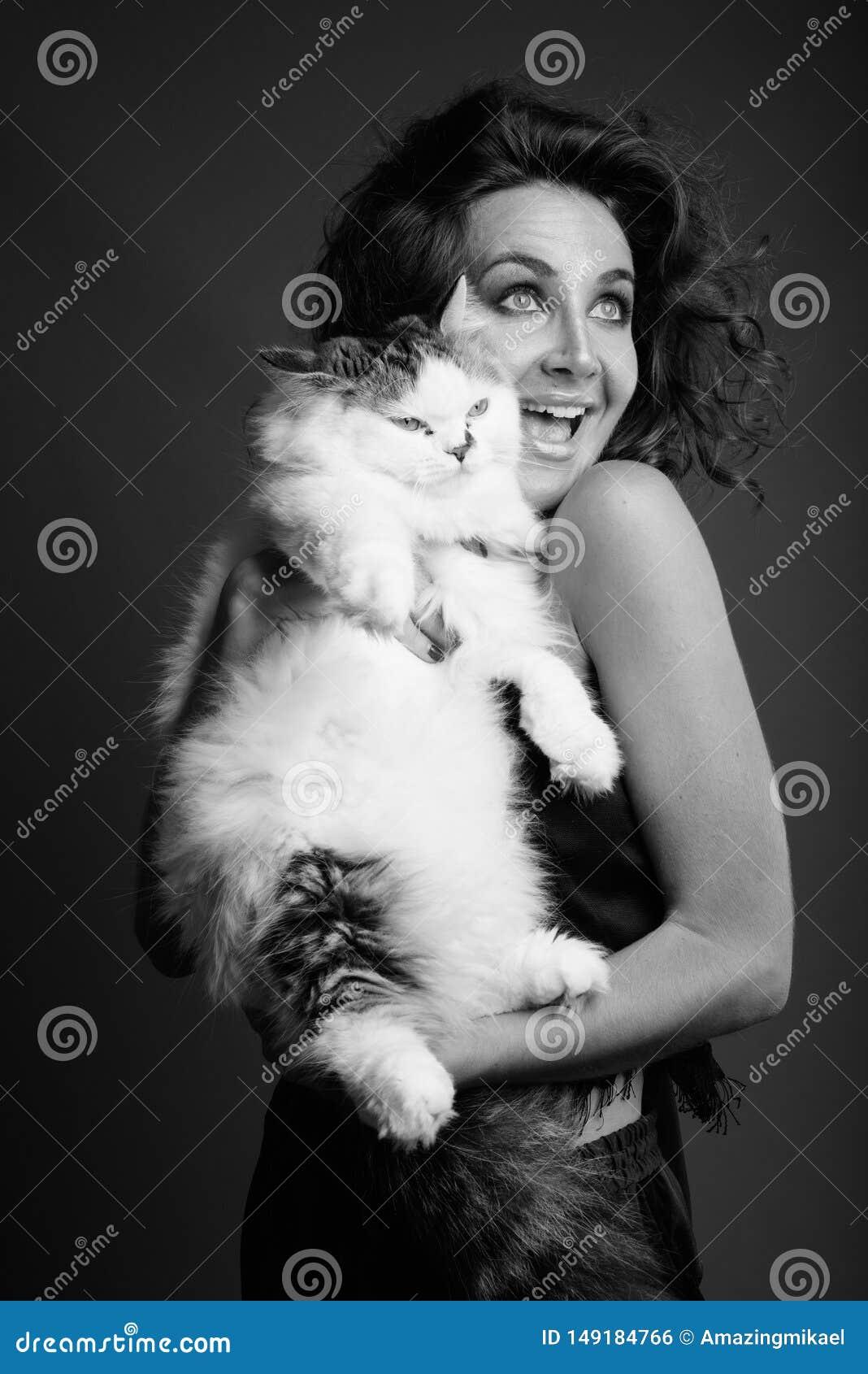 Ung h?rlig kvinna med lockigt h?r som poserar i svartvitt