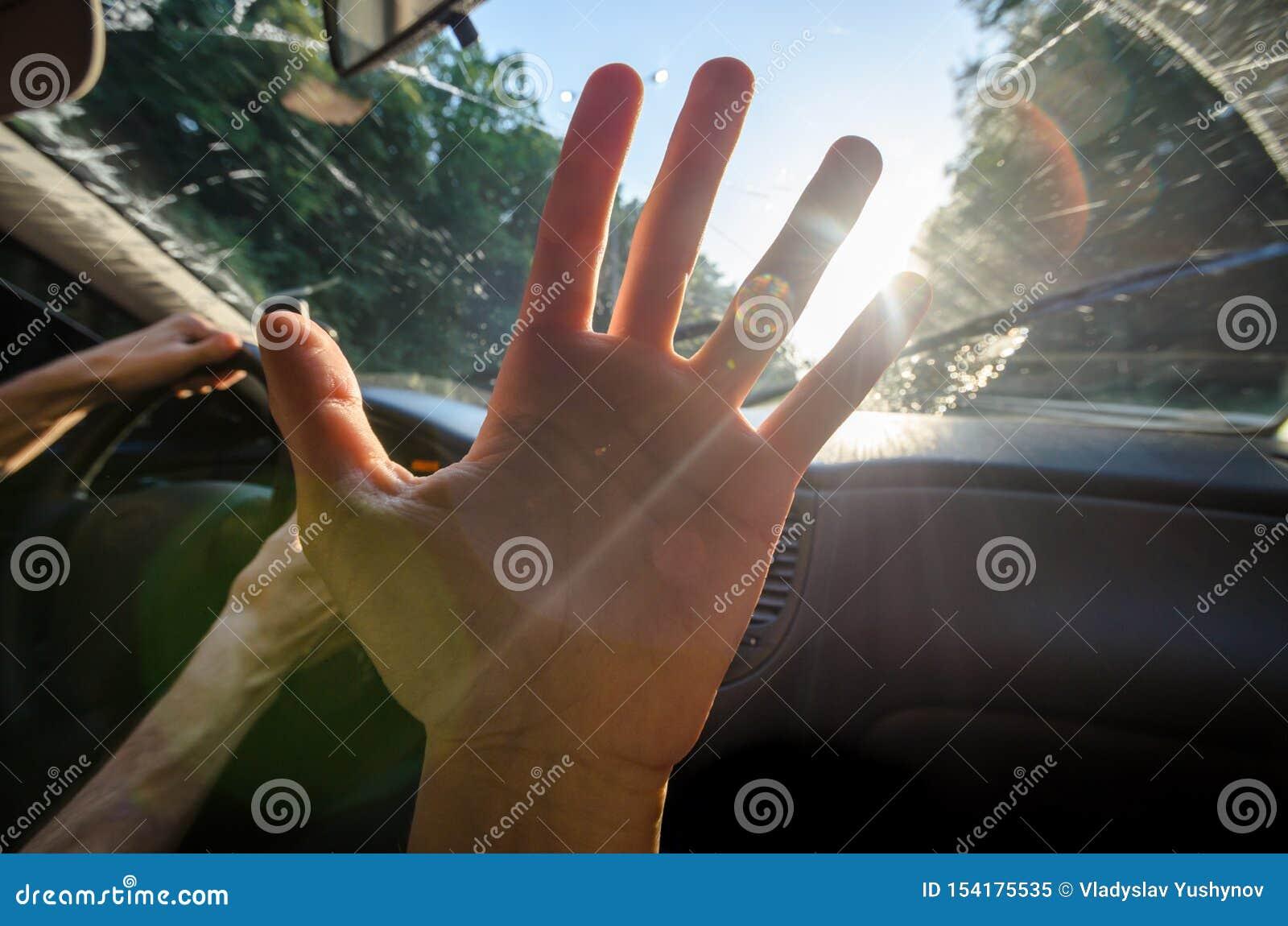 Ung hand mot solen i bilen med viktig