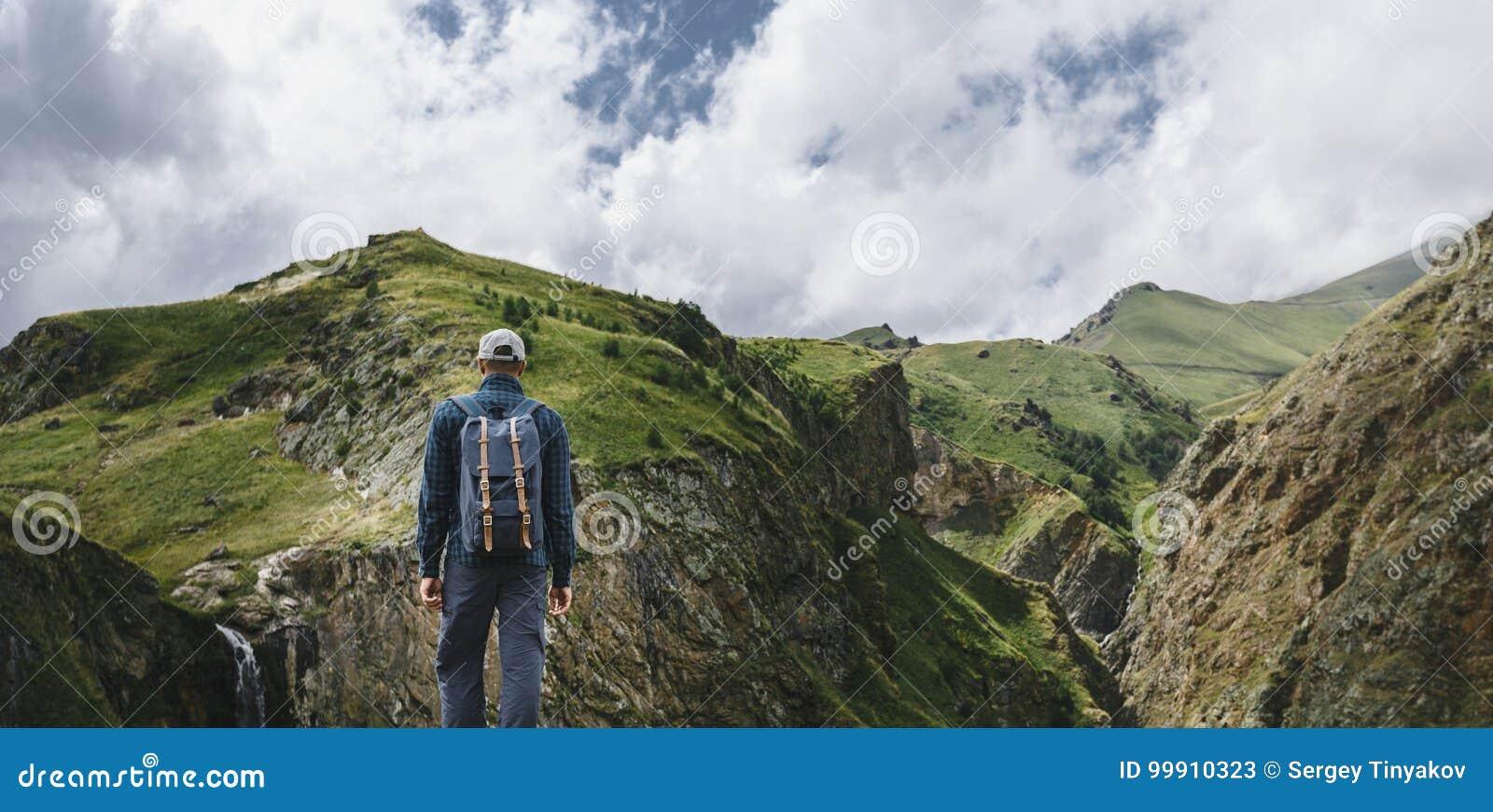 Ung handelsresandeman som överst står av den Cliff In Mountains And Enjoying sikten av naturen, bakre sikt