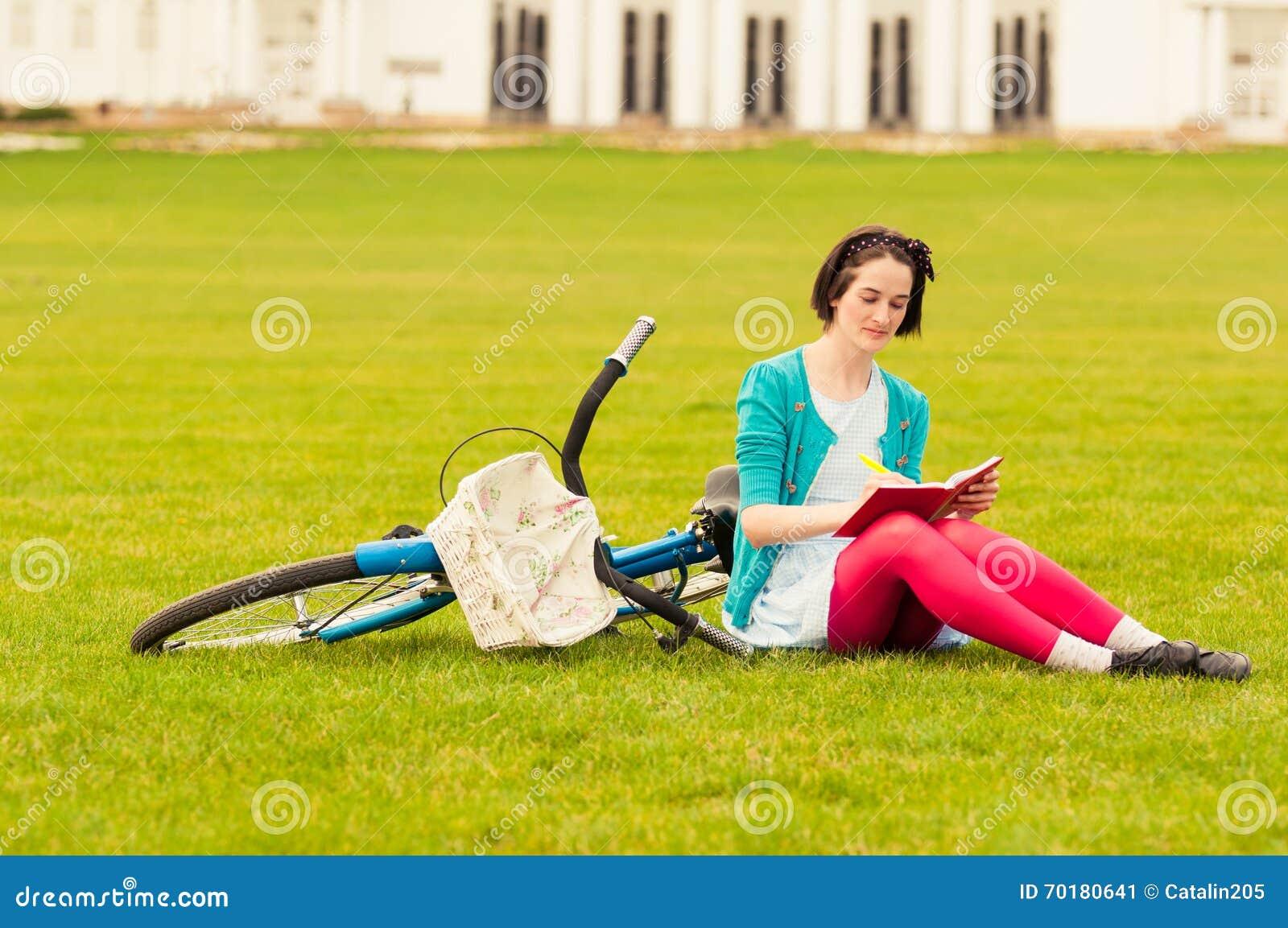 Ung hipsterkvinnlig med cykelhandstil något på anteckningsboken