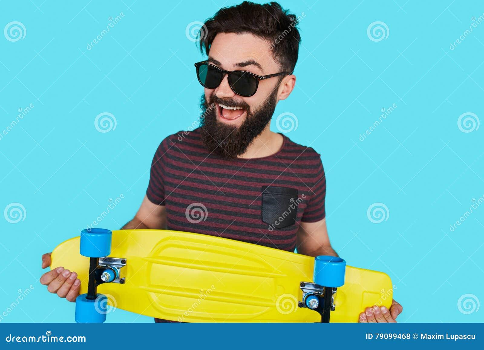 Ung hipsterman med en skateboard