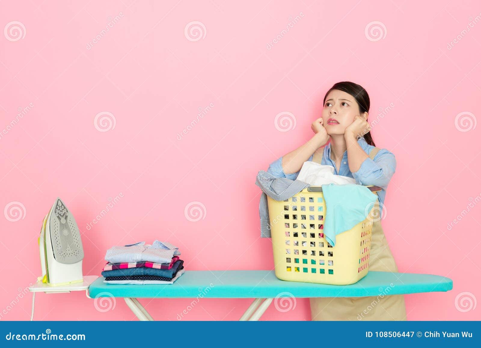 Ung houseworkerkvinna som förbereder strykningkläder