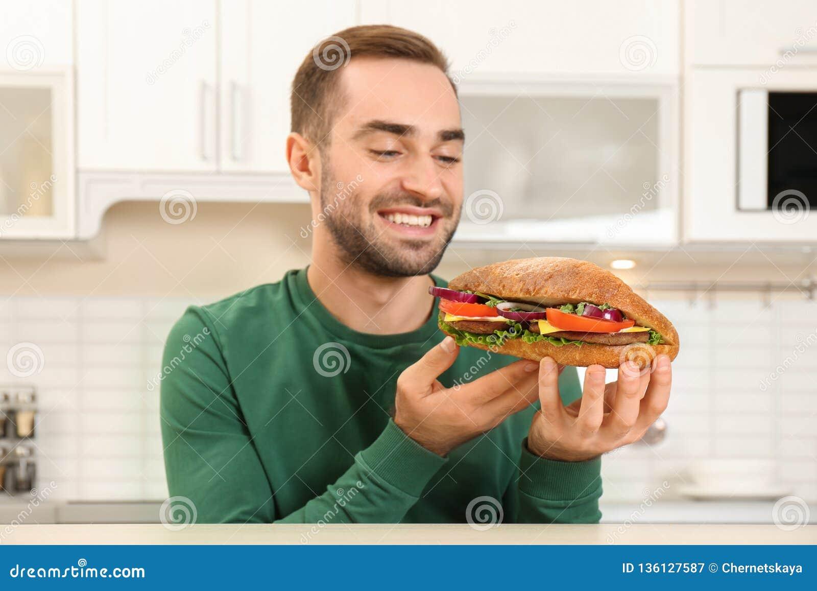 Ung hungrig man som äter den smakliga smörgåsen
