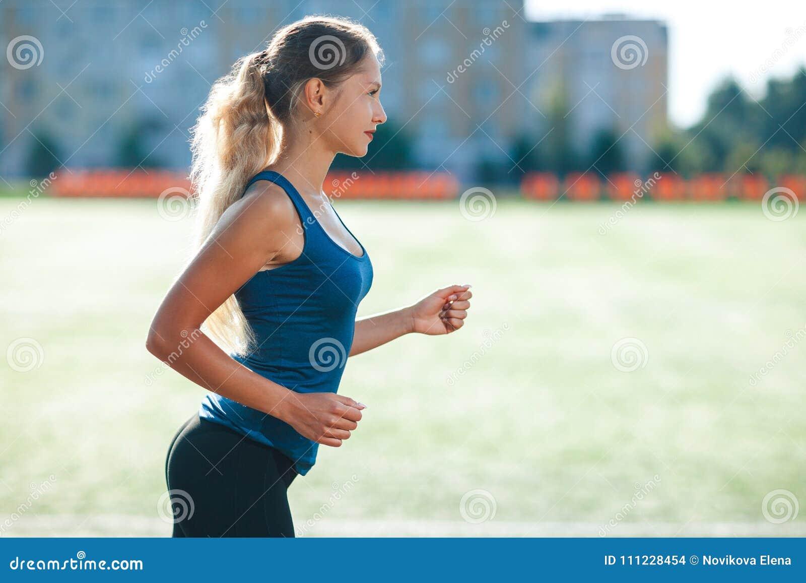 Ung konditionkvinna i en blå skjorta och damasker som kör på ett stadionspår Idrottsman nenflicka som gör övningar på utbildninge