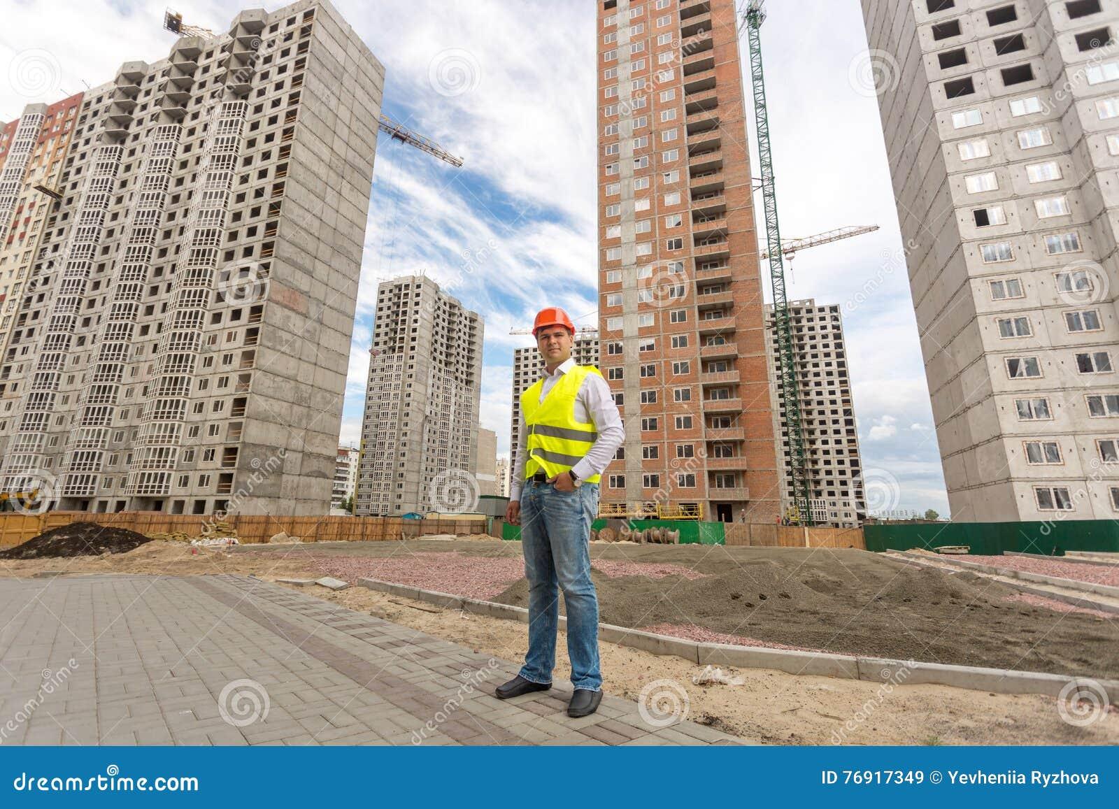 Ung konstruktionstekniker som framme står av byggnader under