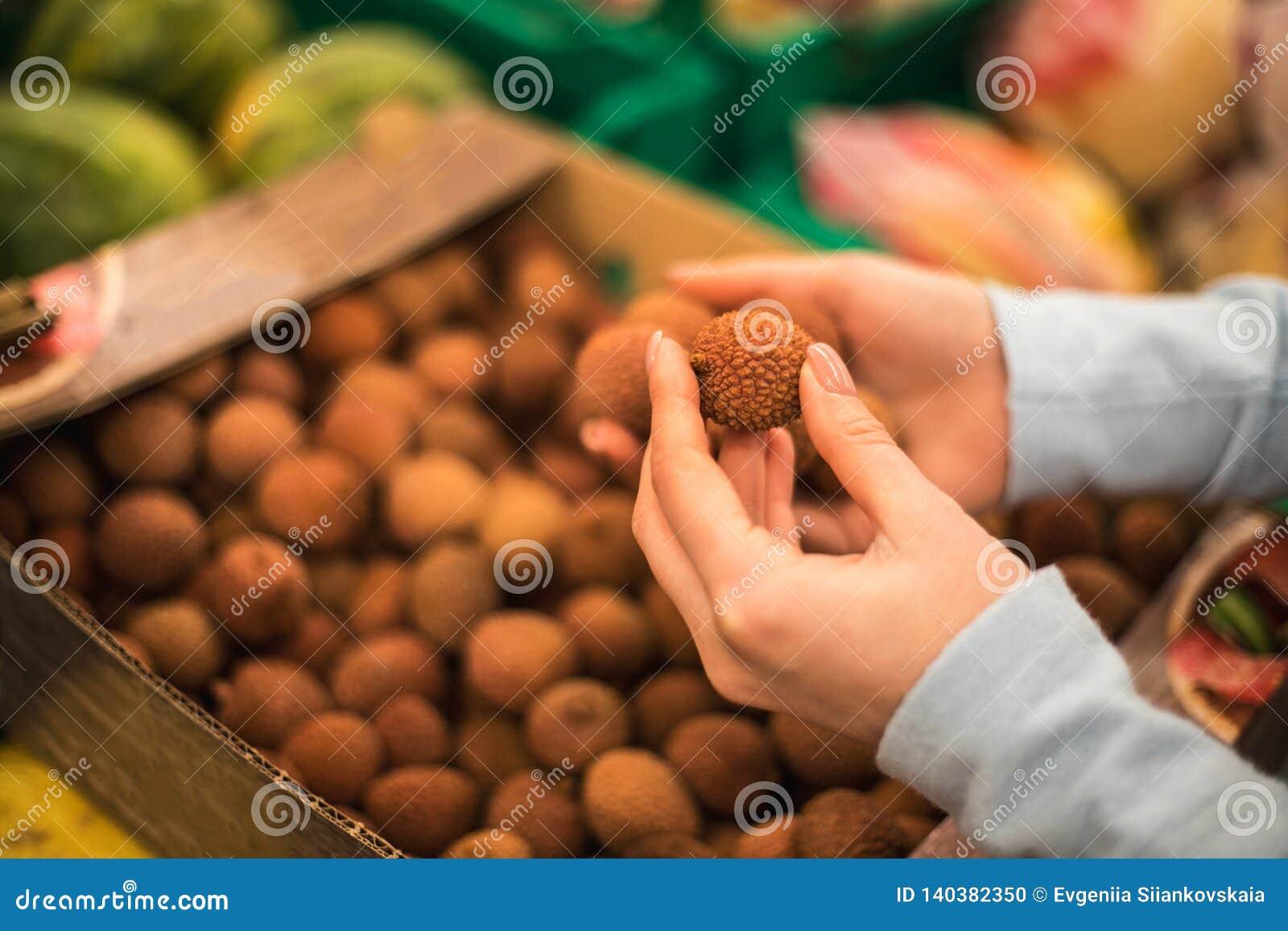 Ung kvinna att välja den nya litchiplommonet på supermarket