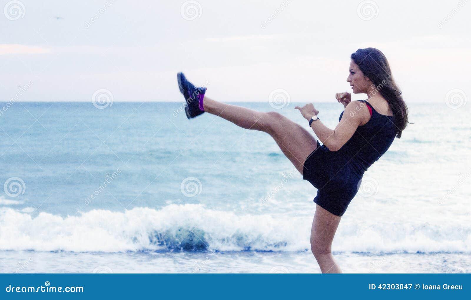 Ung kvinna för sparkboxning som utarbetar på stranden