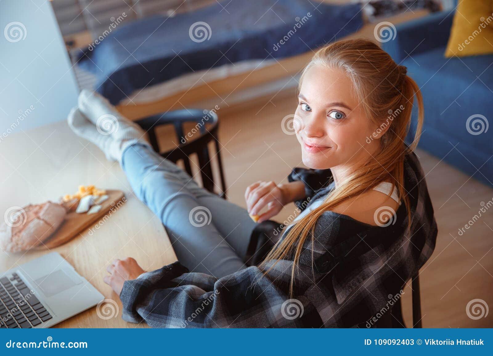 Ung kvinna hemma i köket som äter och använder bärbara datorn