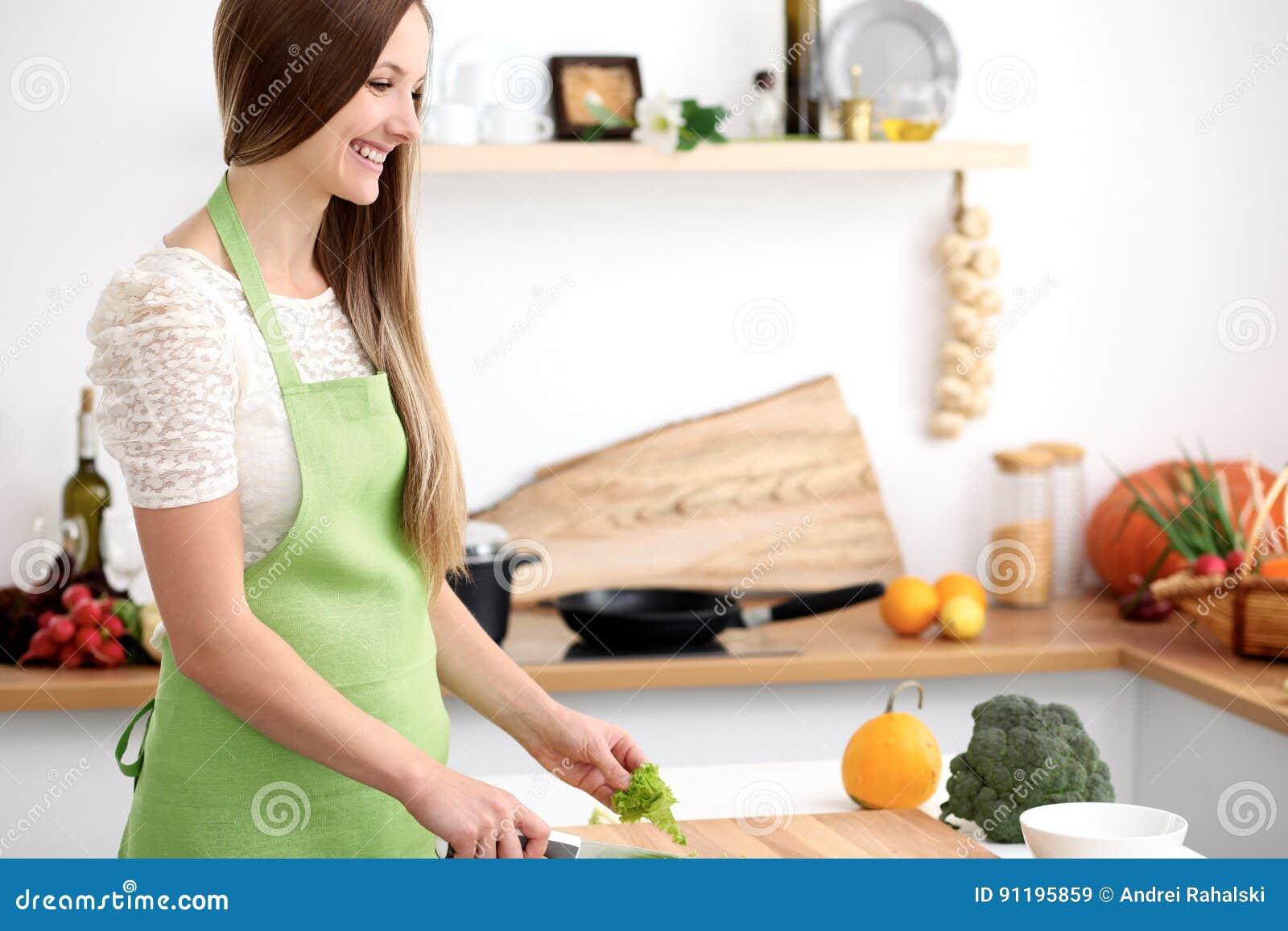 Ung kvinna i den gröna förklädematlagningen i köket Hemmafru som skivar ny sallad