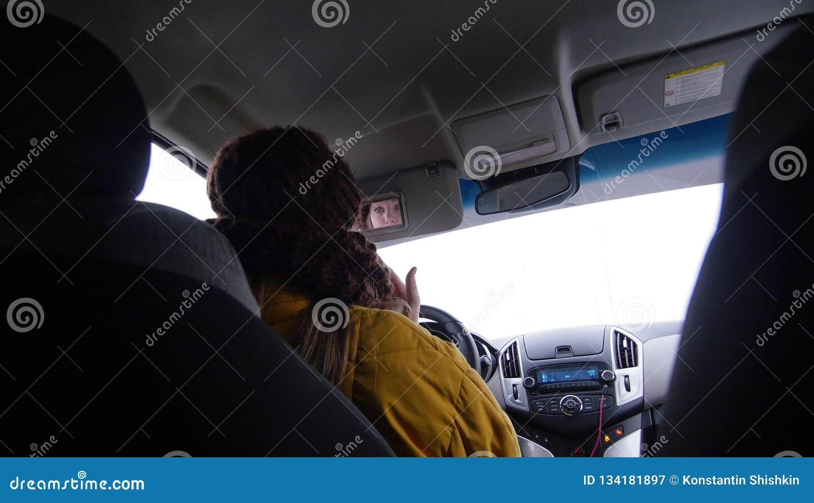 Ung kvinna i det gula omslaget som sitter i bilen och ser på spegeln