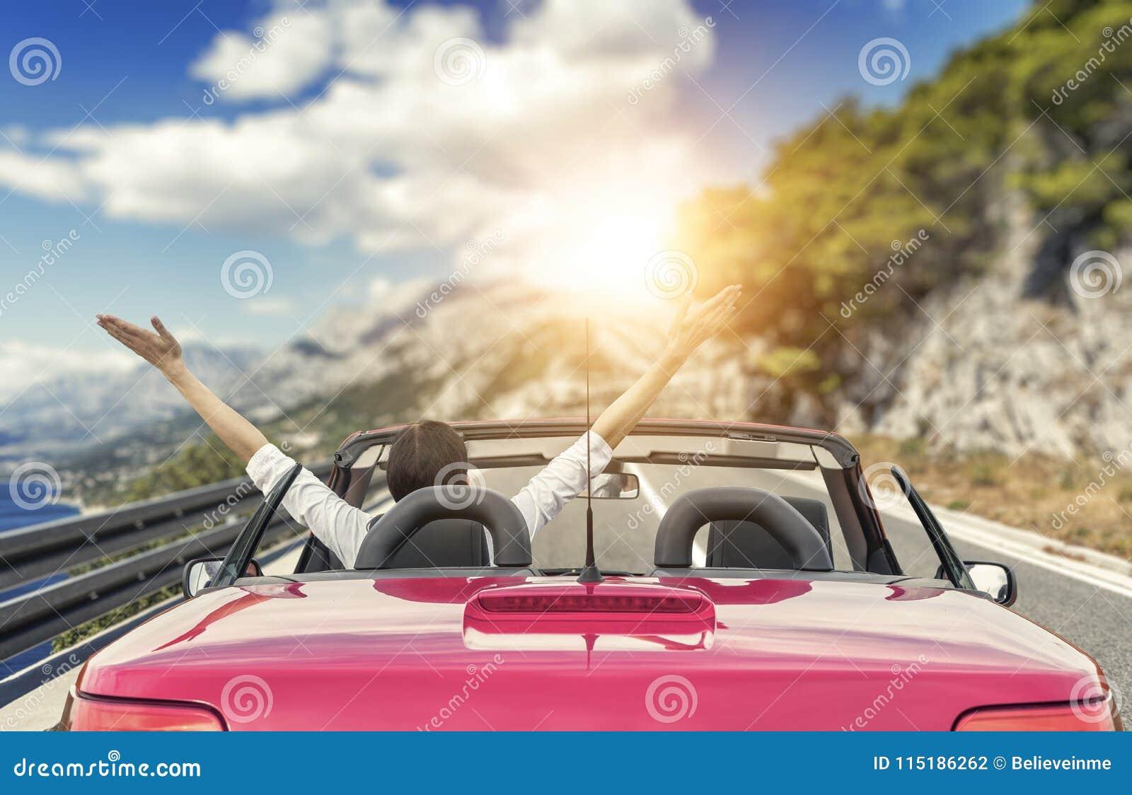 Ung kvinna i en bil på vägen till havet mot en bakgrund av härliga berg på en solig dag