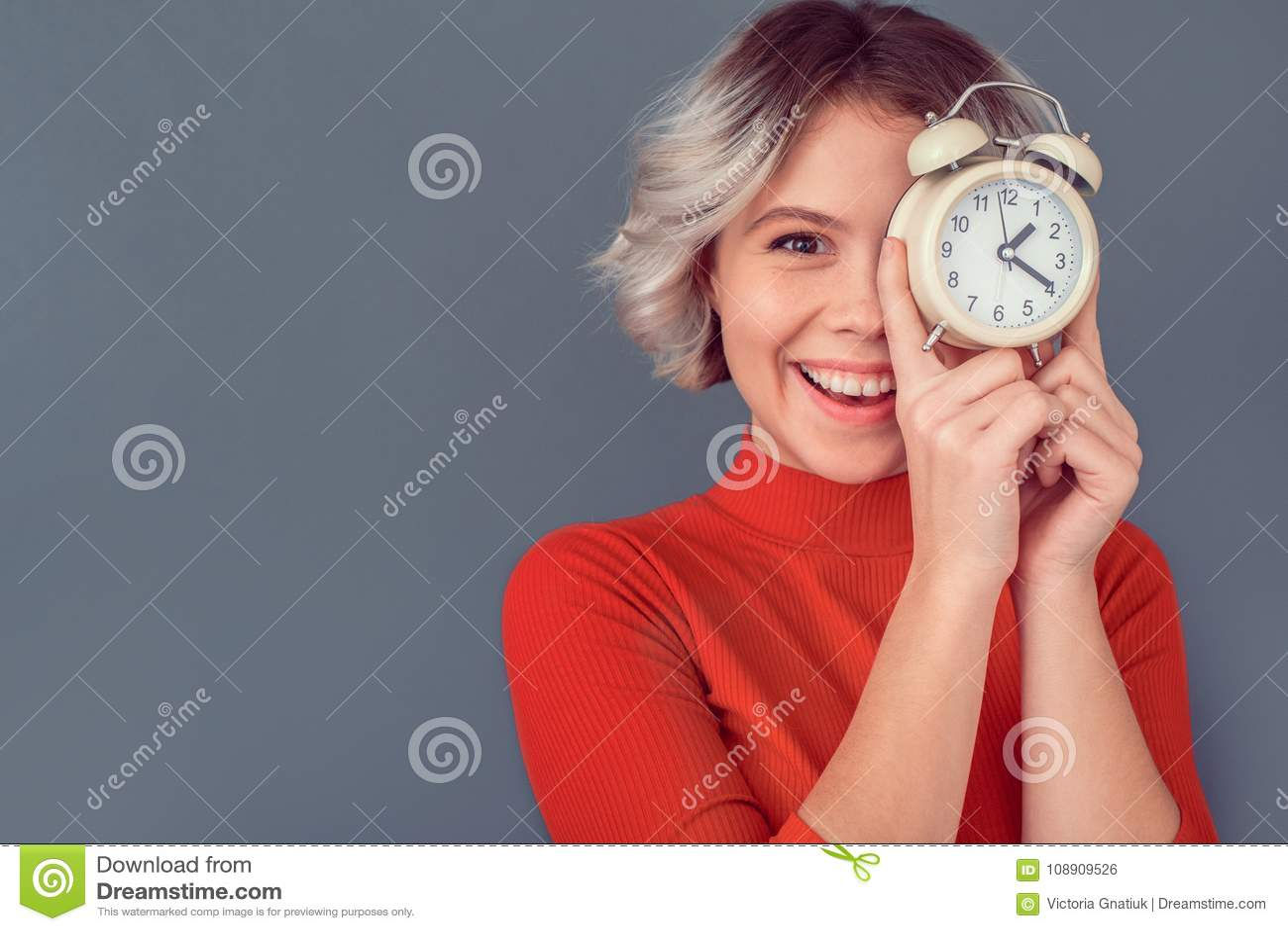 Ung kvinna i en röd blus som isoleras på grå väggtidledning