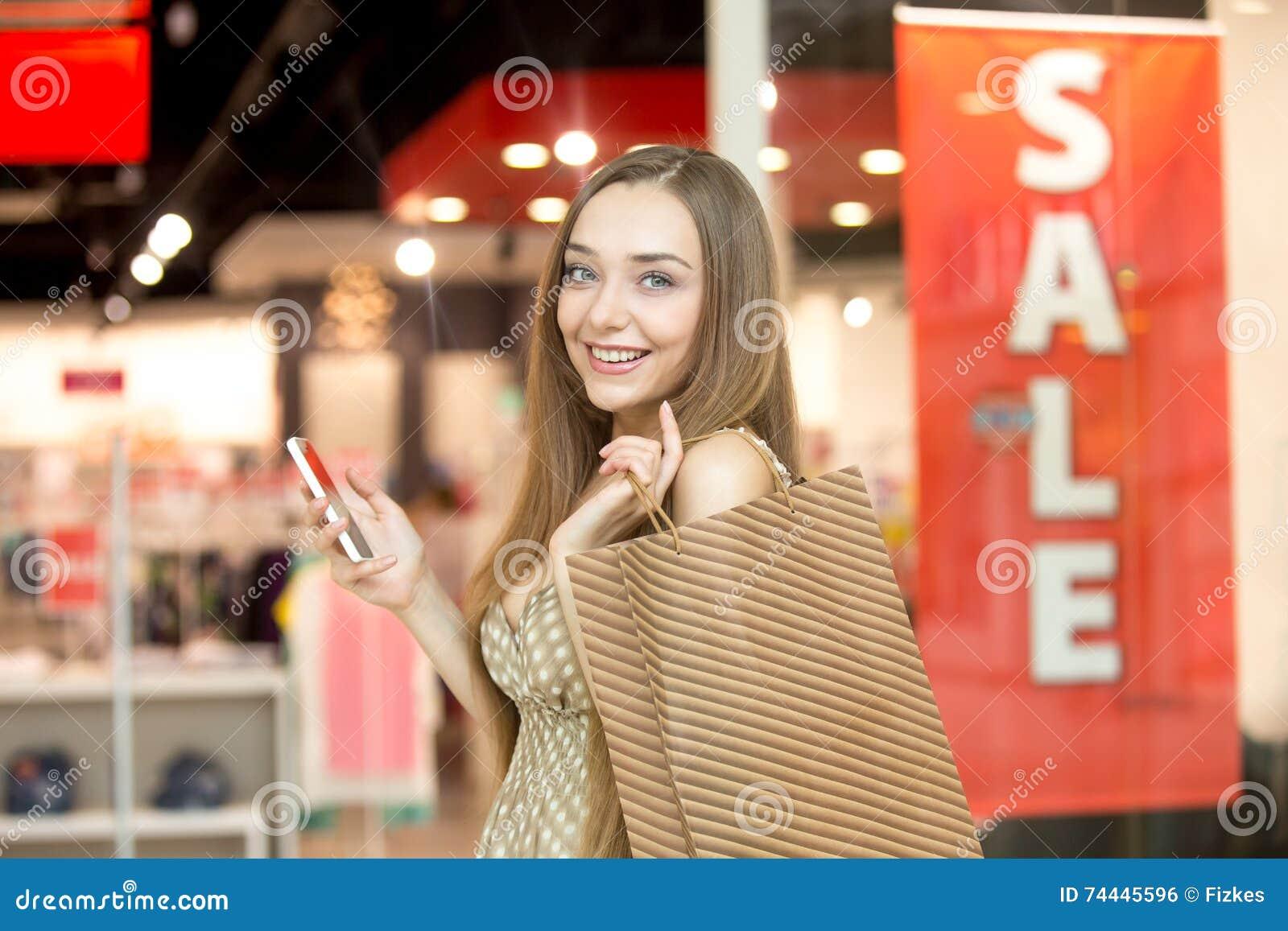 Ung kvinna i en shoppingmitt som rymmer le för telefon