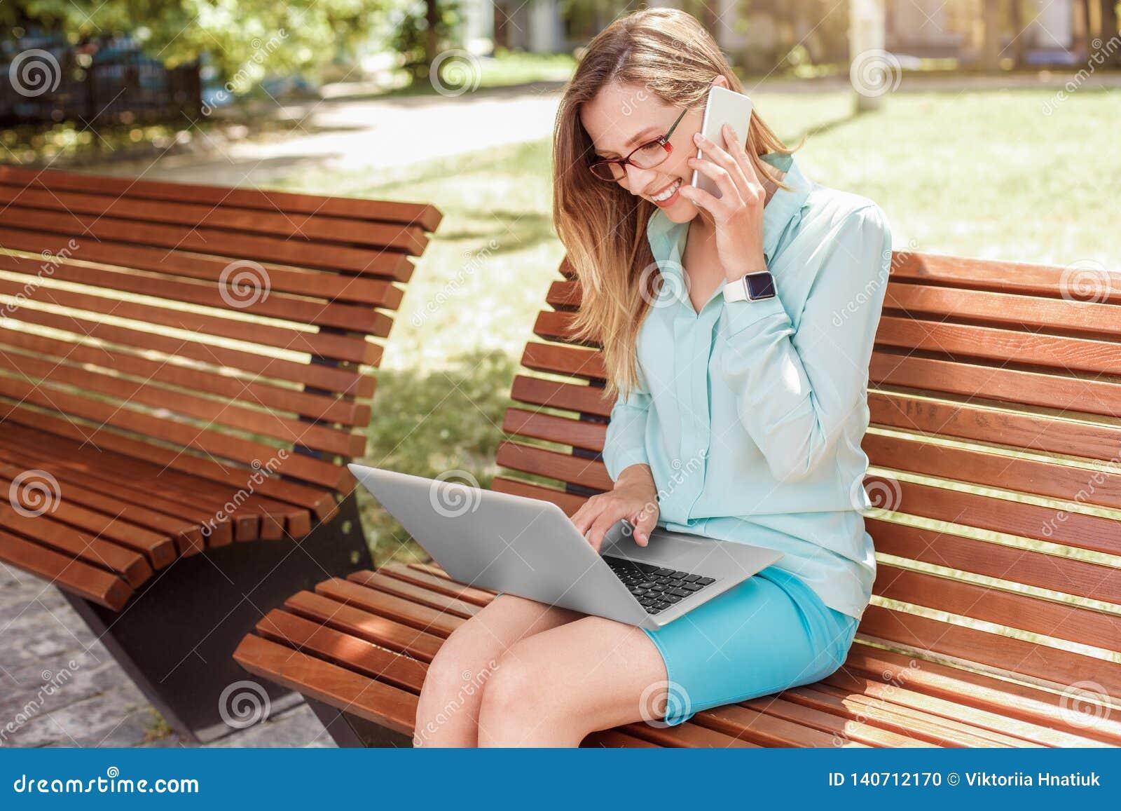 Ung kvinna i glasögon som sitter på bänken som arbetar på svarande påringning för bärbar dator på glad sidosikt för smartphone