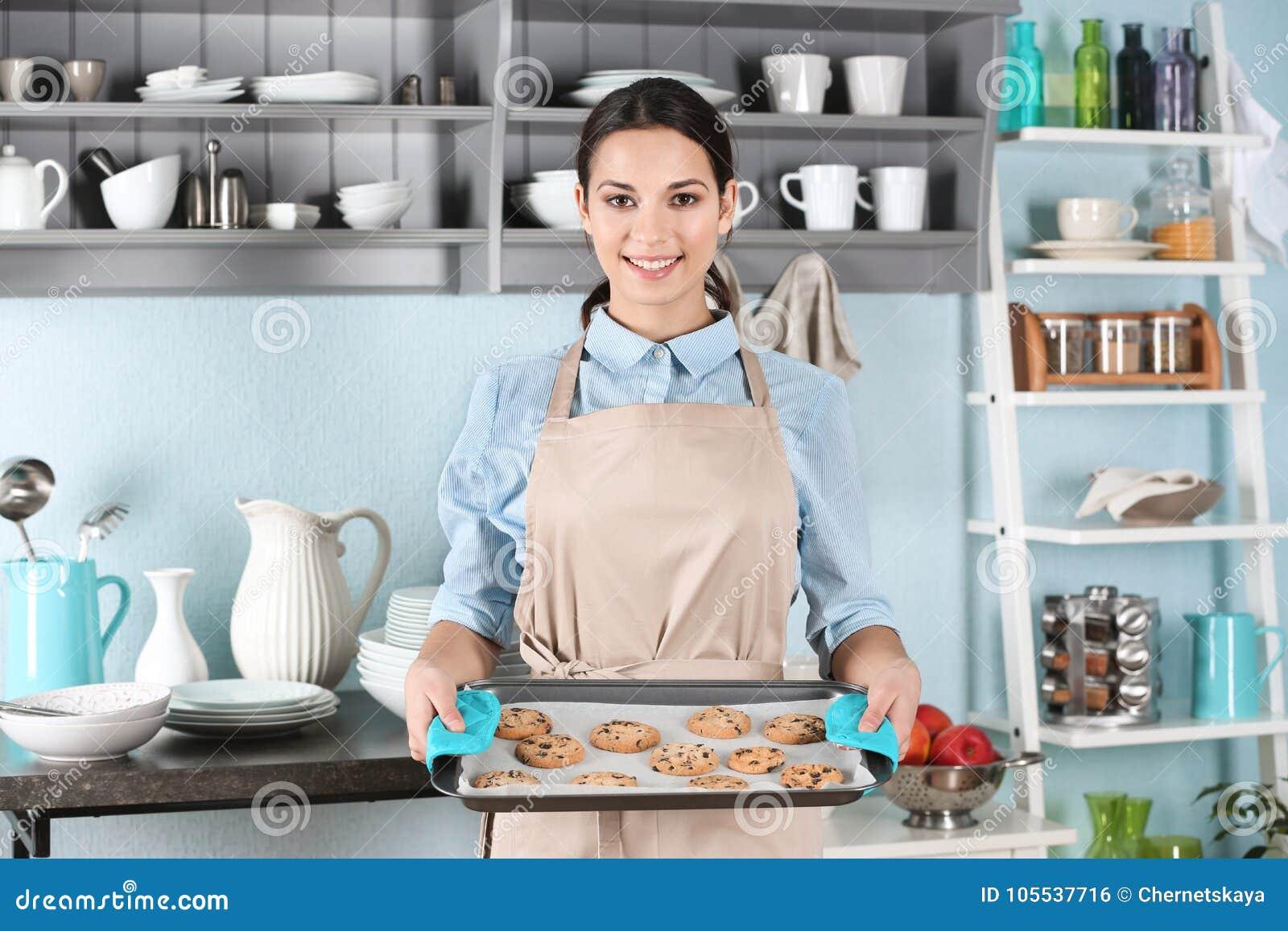 Ung kvinna i hållande bakplåt för förkläde med kakor