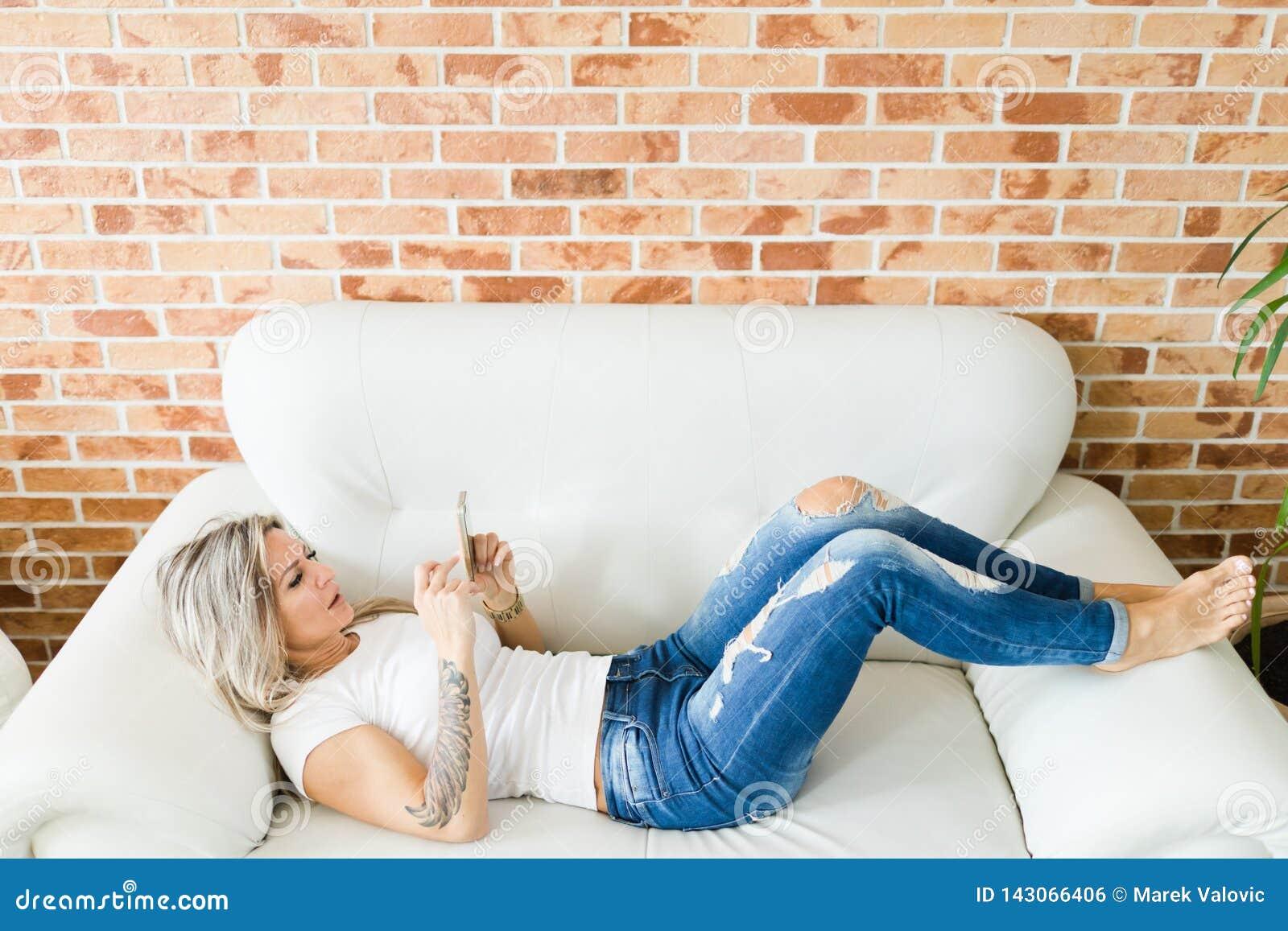 Ung kvinna i jeans genom att använda den smarta telefonen som ligger på den vita soffan