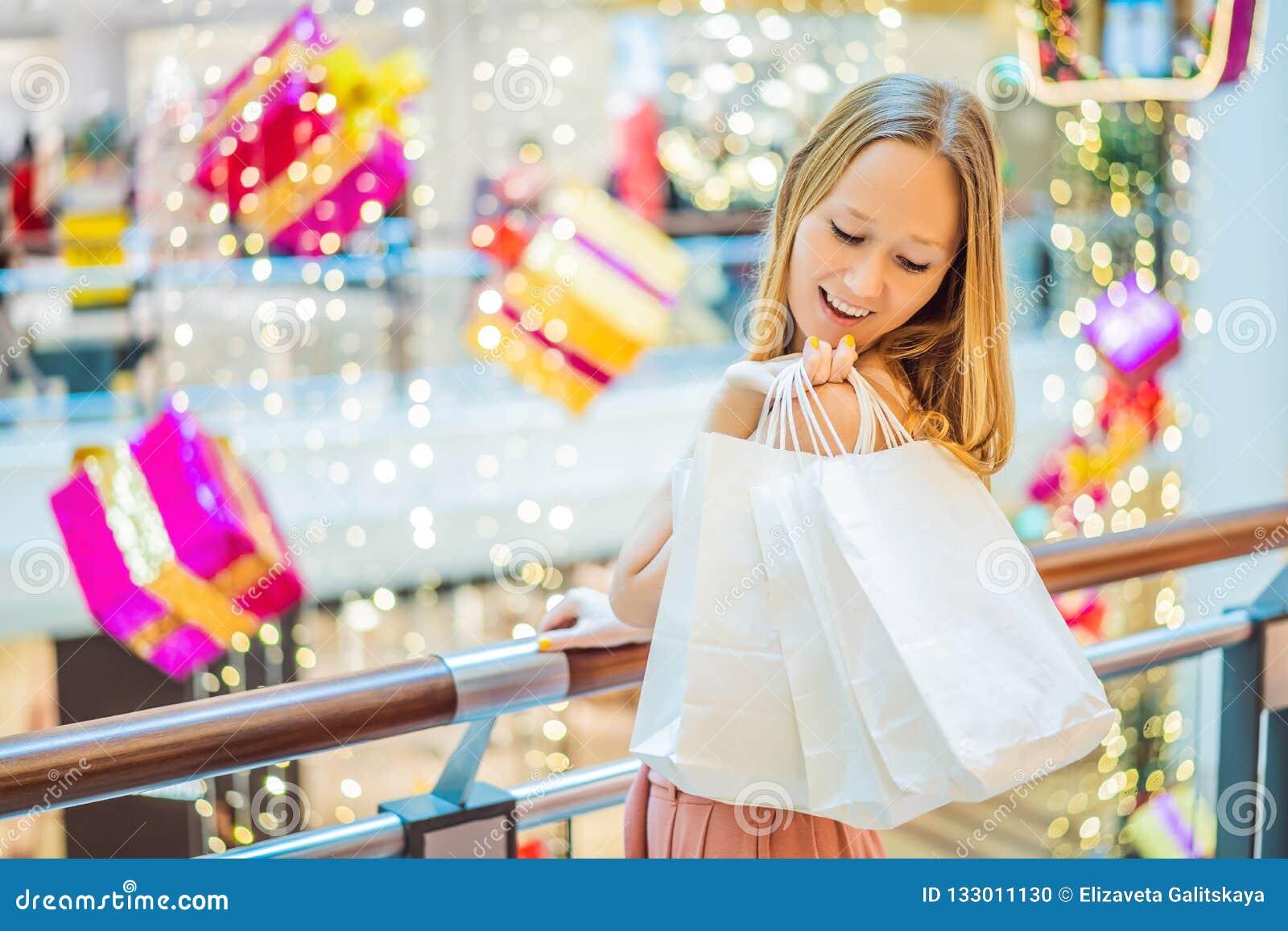Ung kvinna i julgalleria med julshopping Skönhetbu