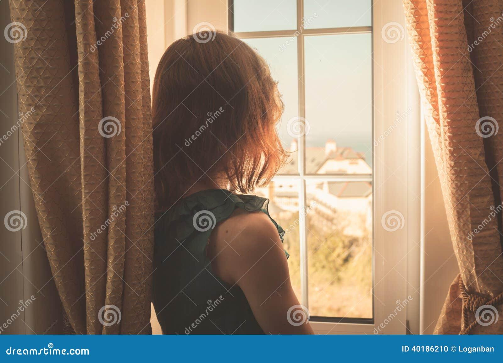 Ung kvinna i klänningen som ut ser fönstret