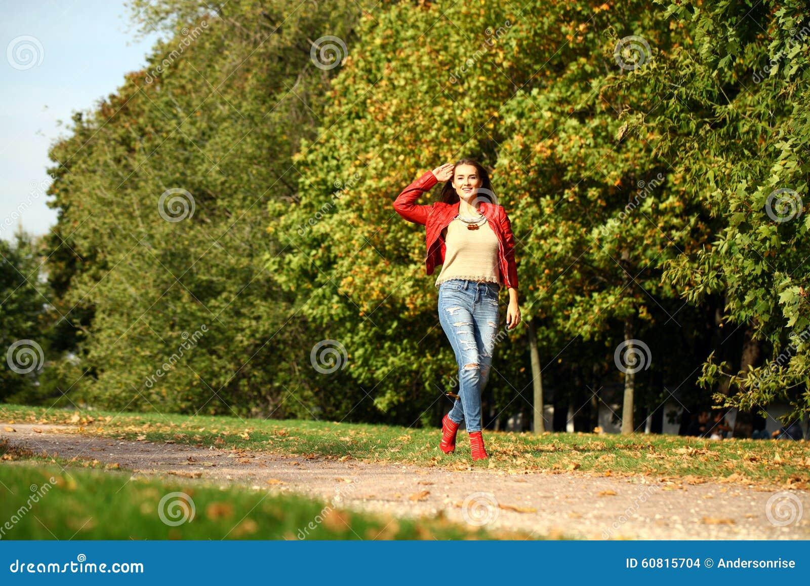 Ung kvinna i omslag och jeans för mode som rött går i autu