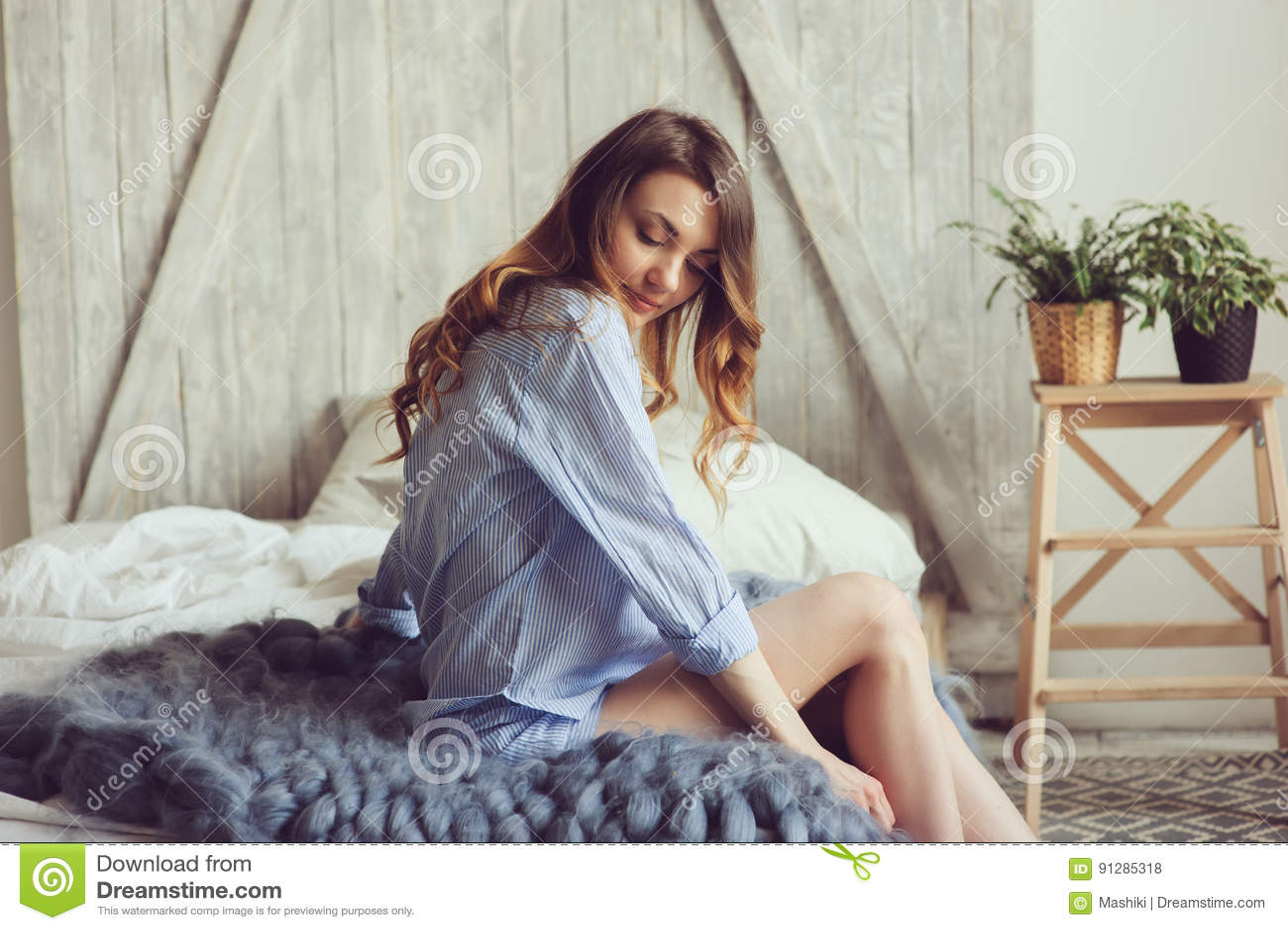 Ung kvinna i pajamavak, upp i morgonen i hemtrevligt scandinavian sovrum och att ligga på säng med stack filten i storformat