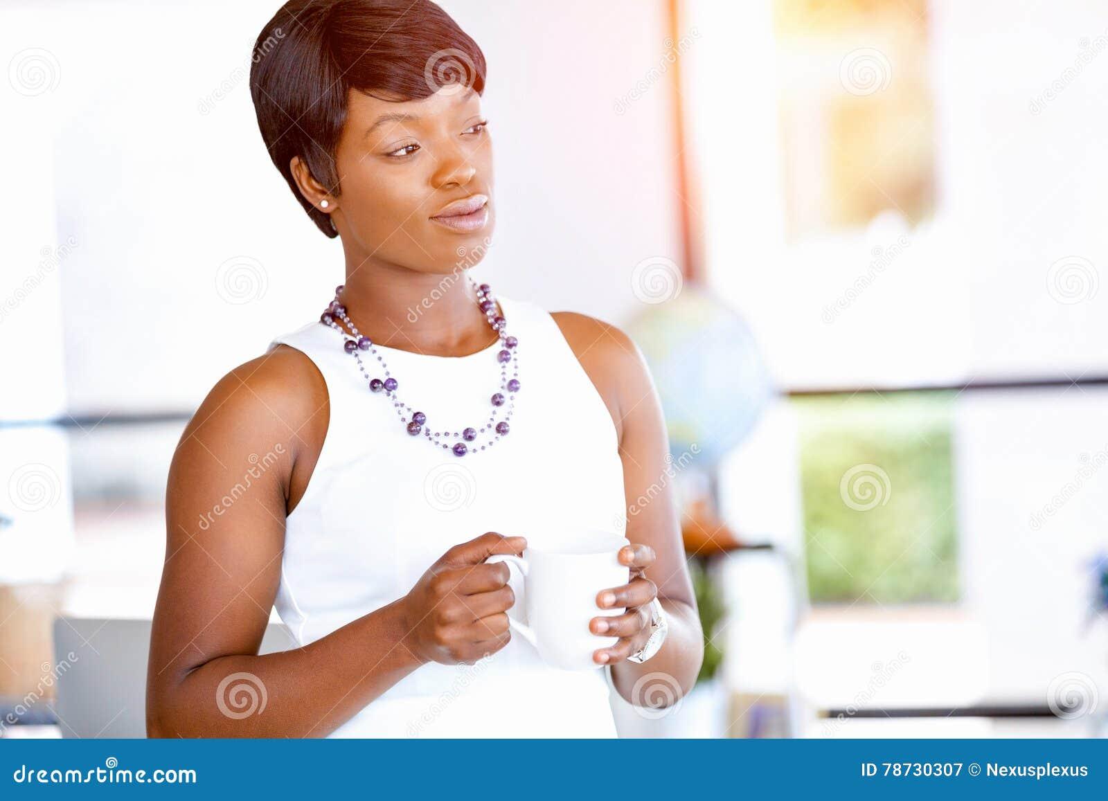 Ung kvinna i regeringsställning som rymmer koppen