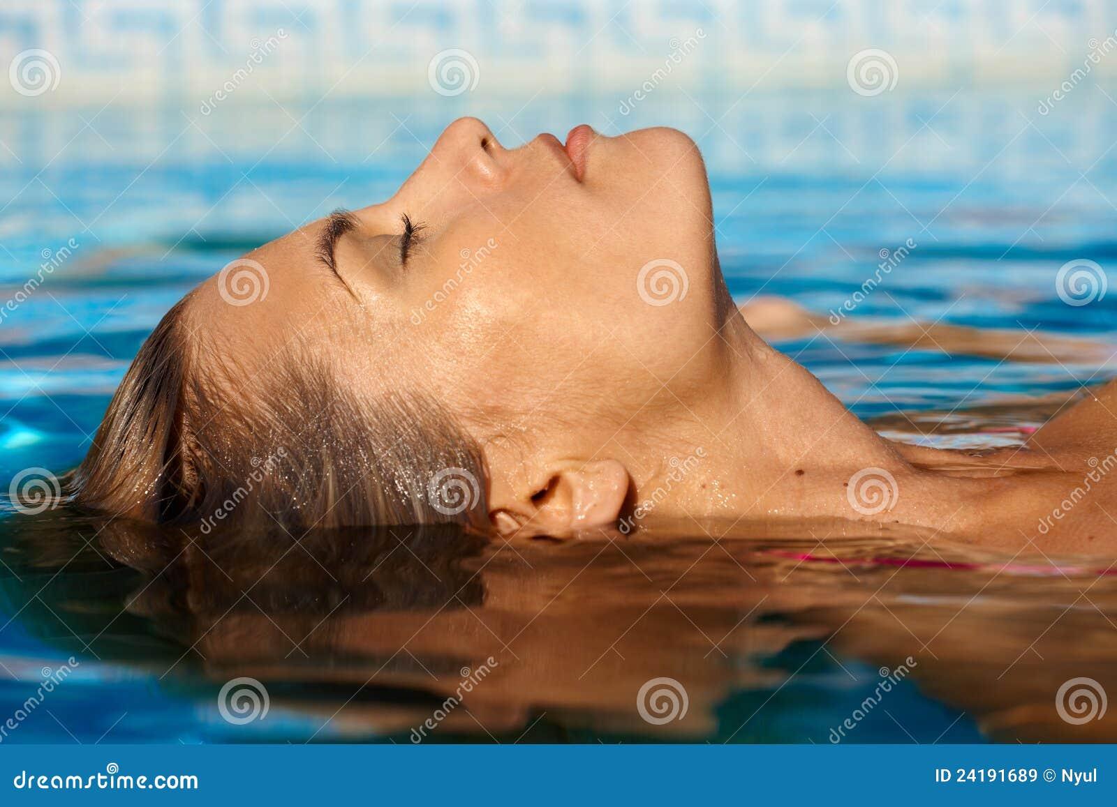 Ung kvinna i simbassäng