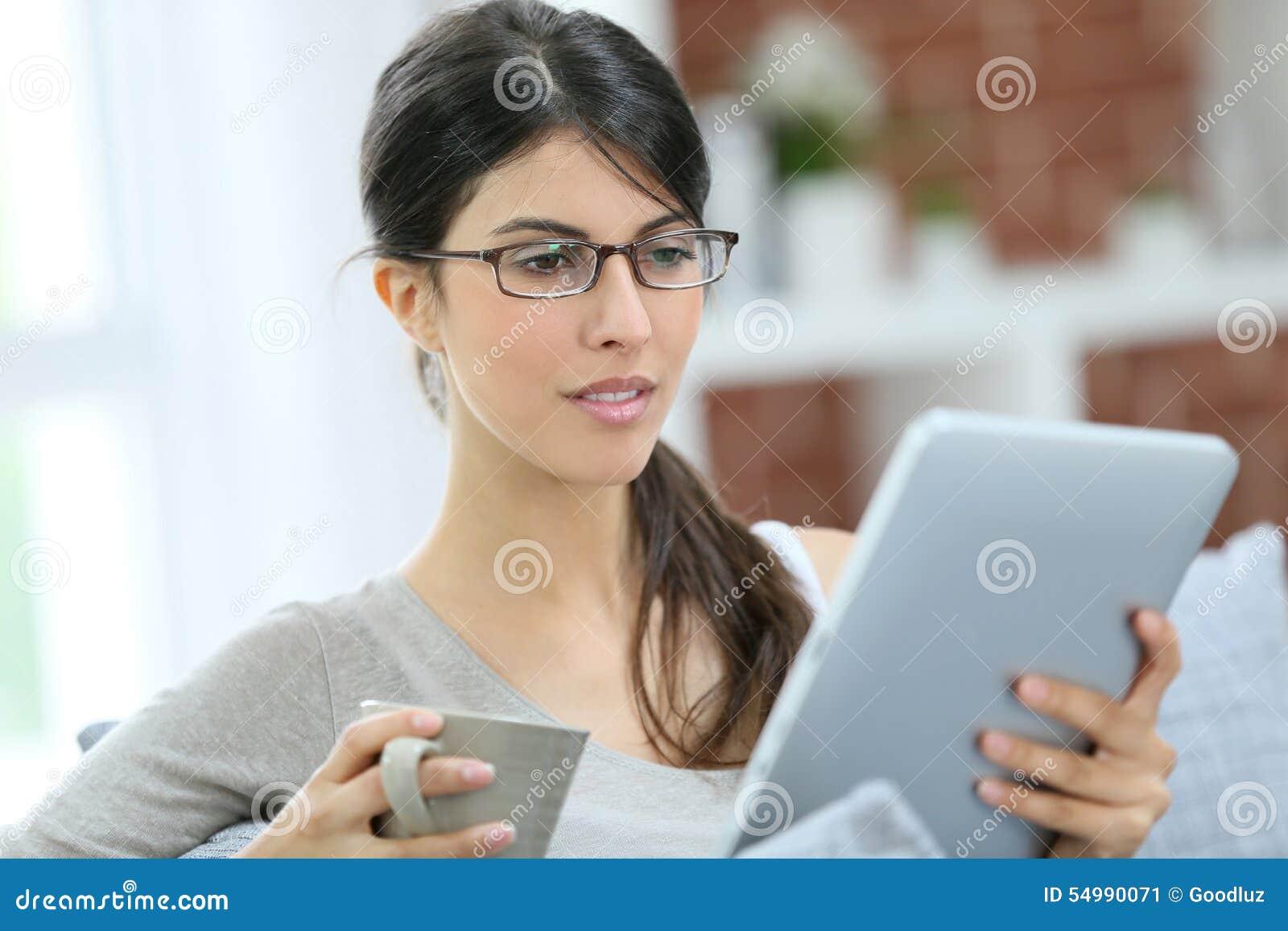 Ung kvinna i soffa genom att använda minnestavlan