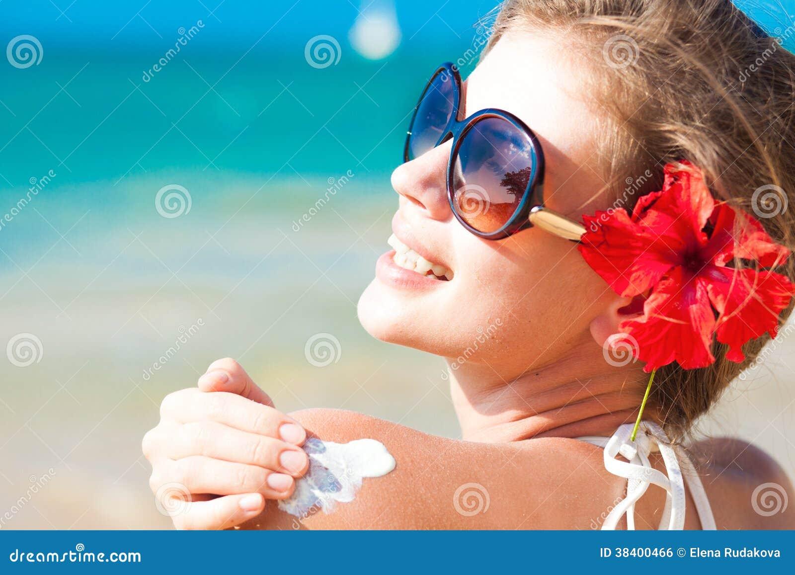 Ung kvinna i solglasögon som sätter på solkräm