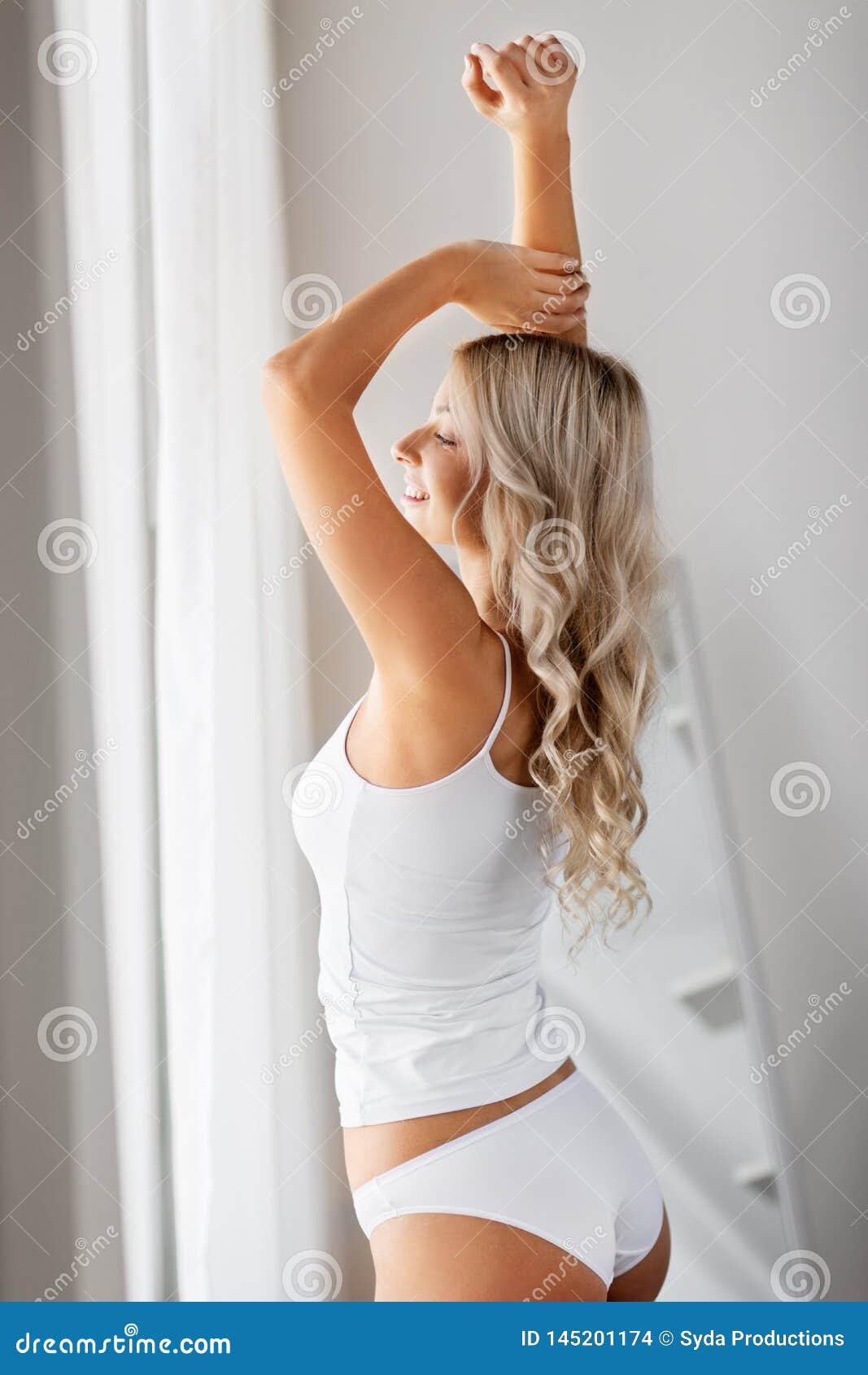 Ung kvinna i underkl?derna som str?cker det hemmastadda f?nstret