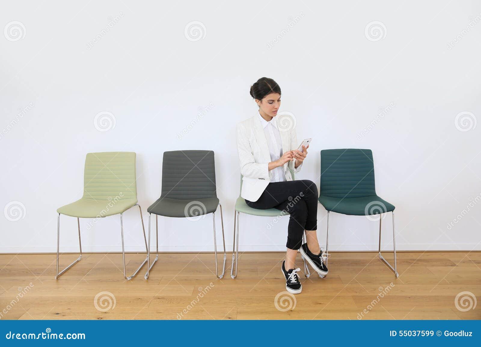 Ung kvinna i väntande rum genom att använda smartphonen