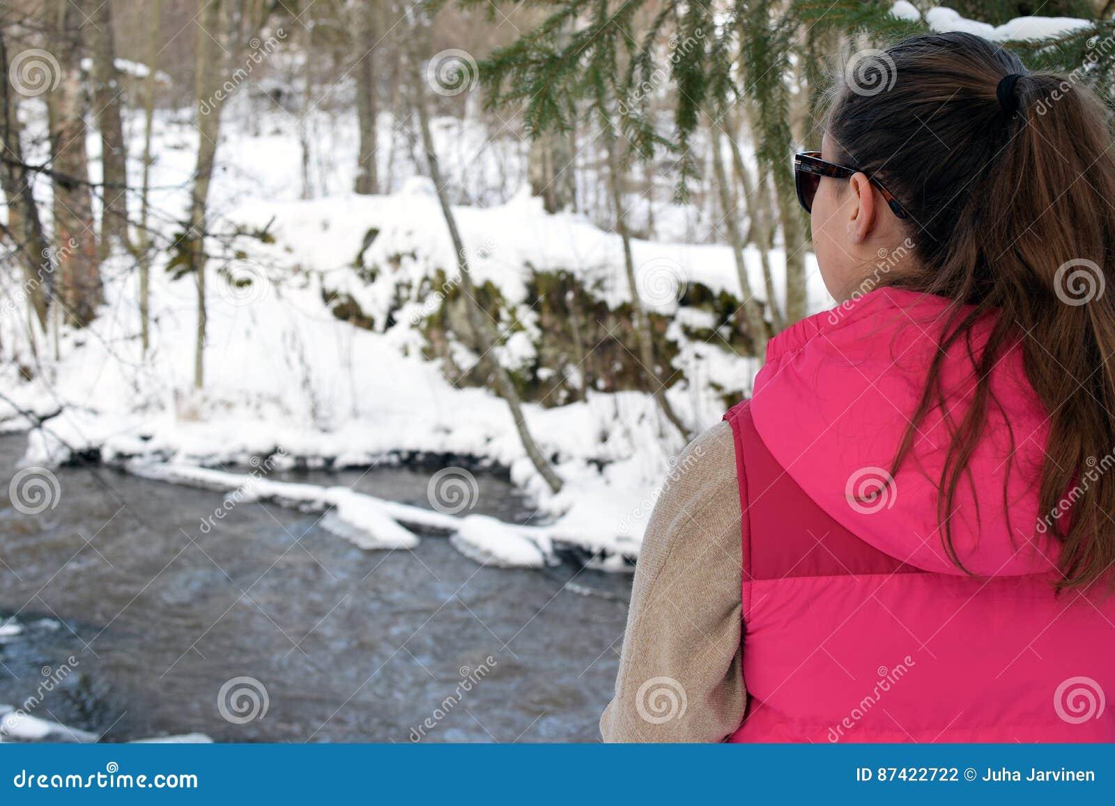 Ung kvinna i vintrig skog