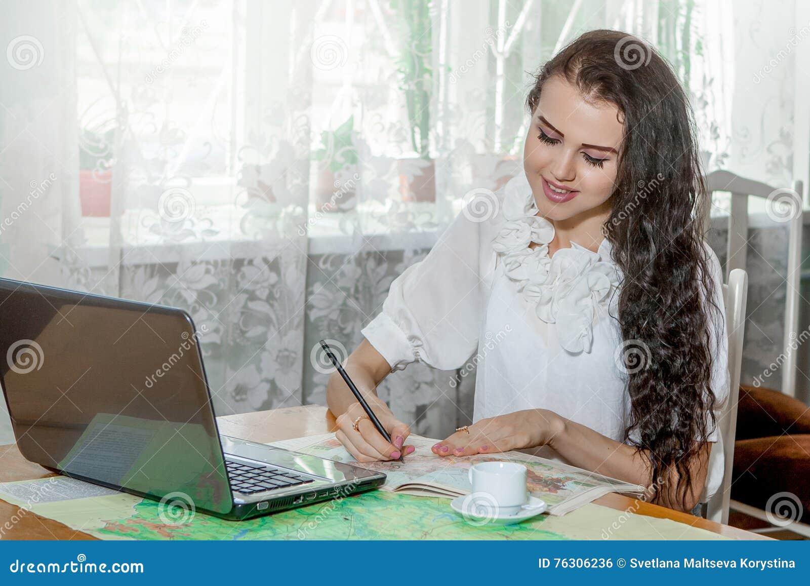 Ung kvinna med bärbara datorn och översikten