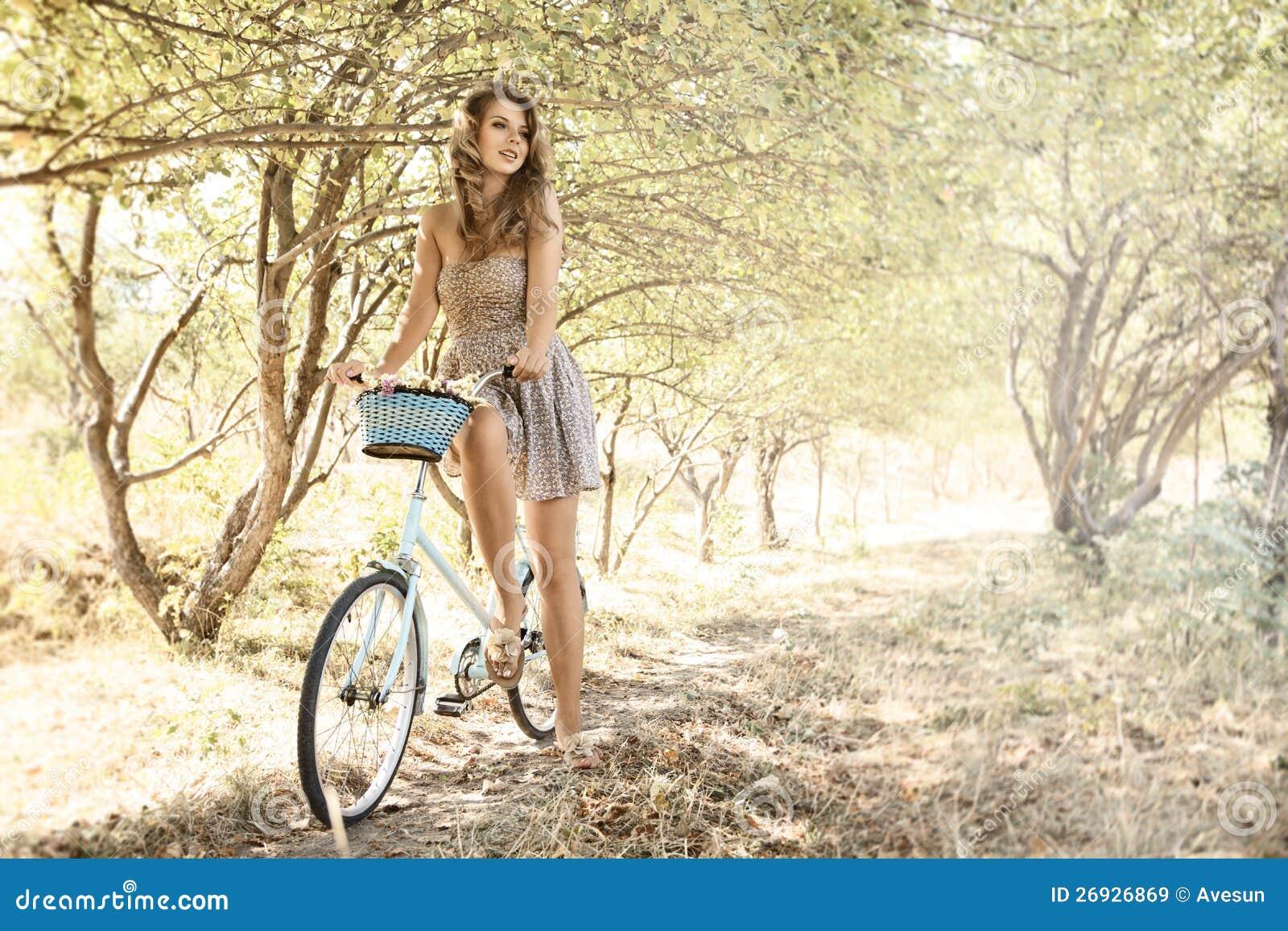 Ung kvinna med cykeln i en park