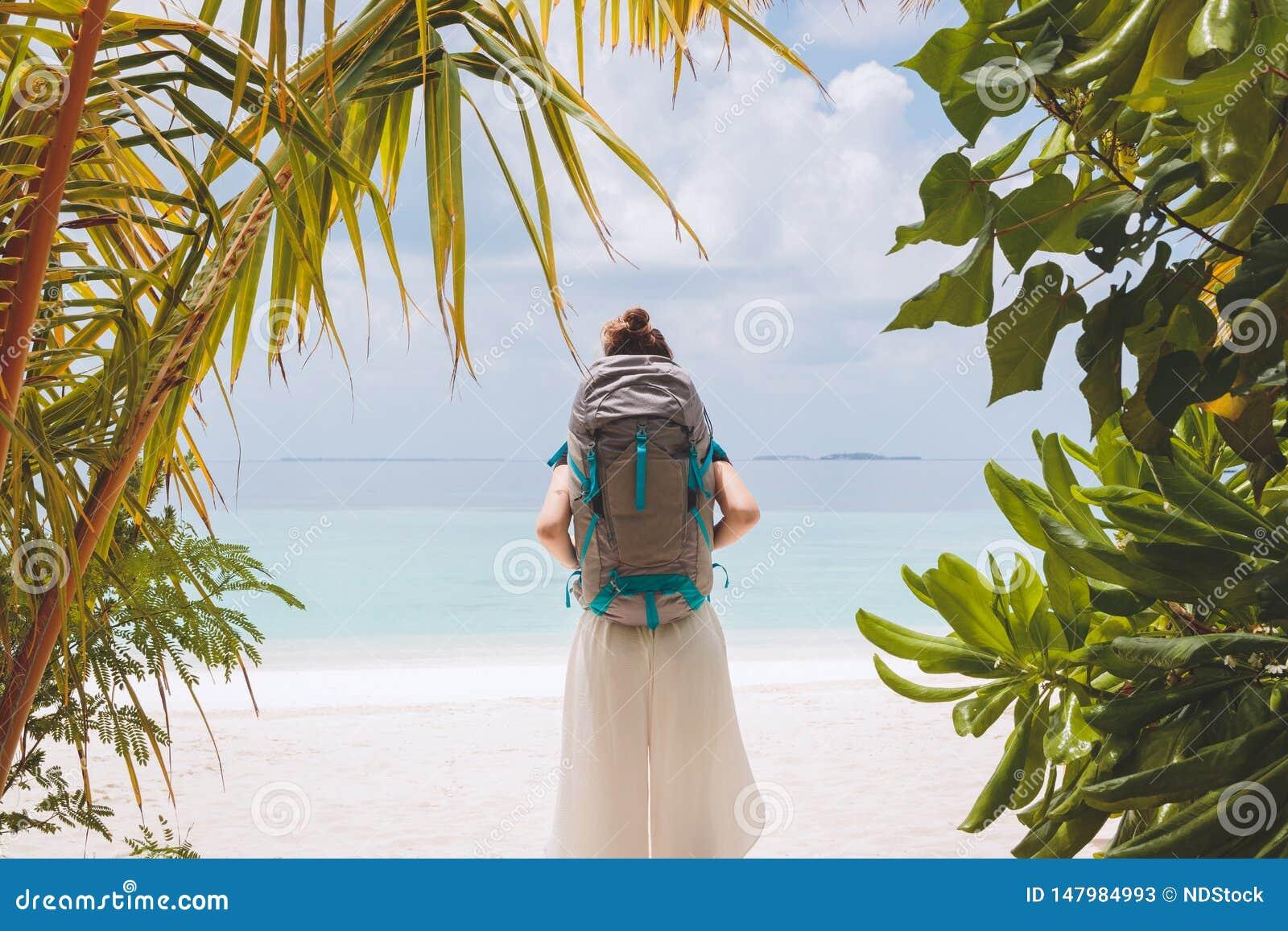Ung kvinna med den stora ryggsäcken som går till stranden i en tropisk feriedestination