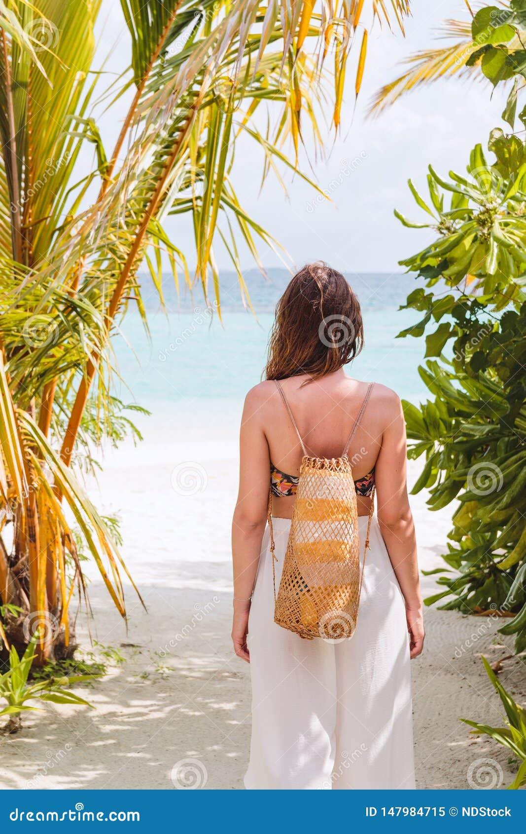 Ung kvinna med en handduk som g?r till stranden i en tropisk destination