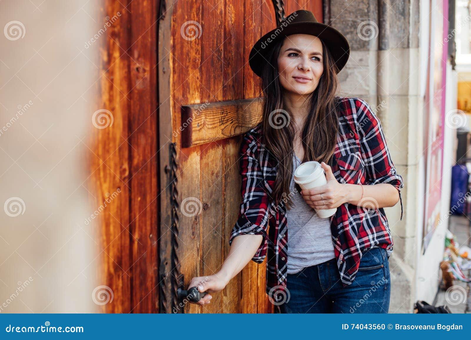Ung kvinna med en hatt bredvid en gammal trädörr