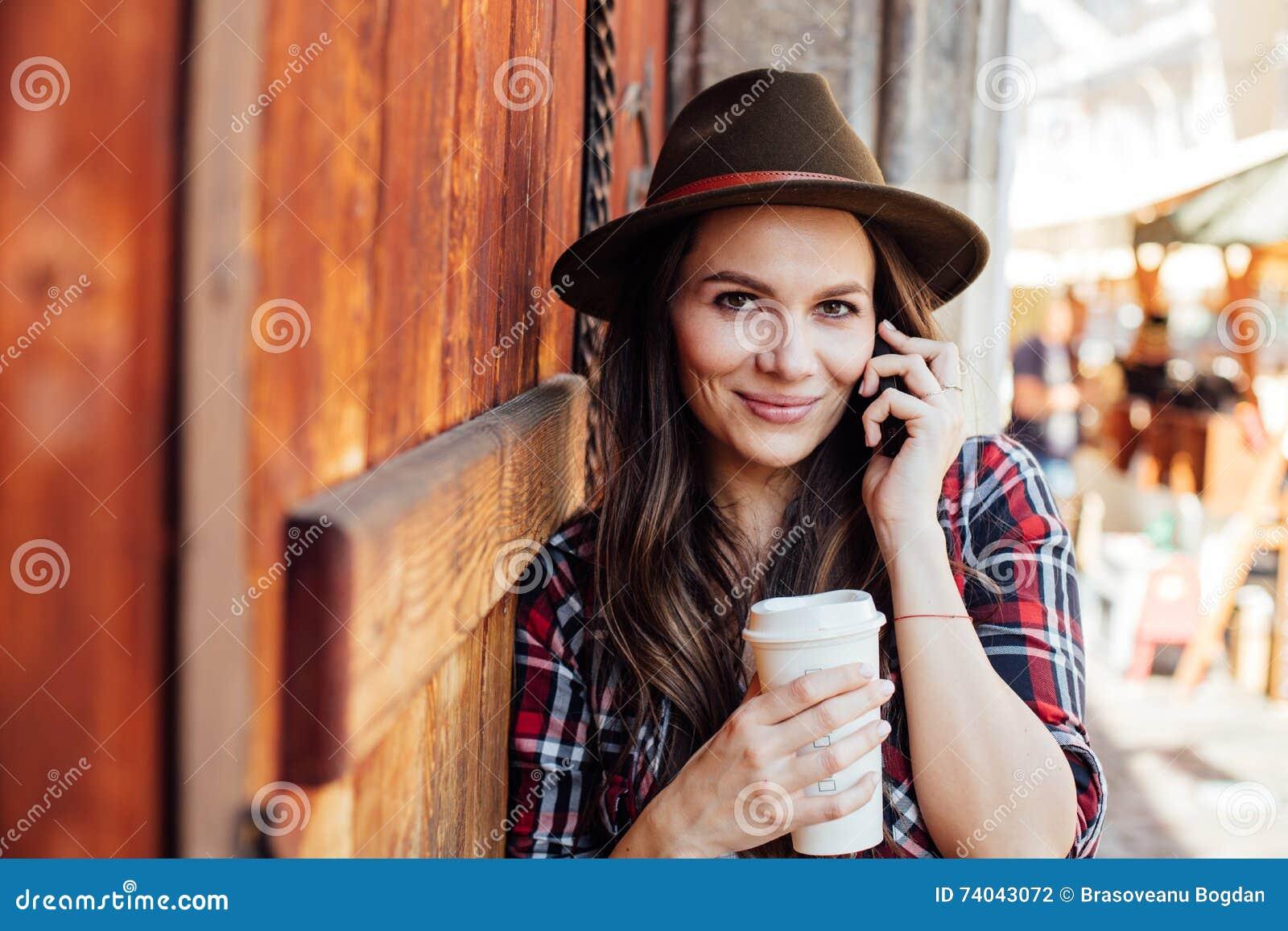 Ung kvinna med en hatt bredvid en gammal trädörr som talar på cel