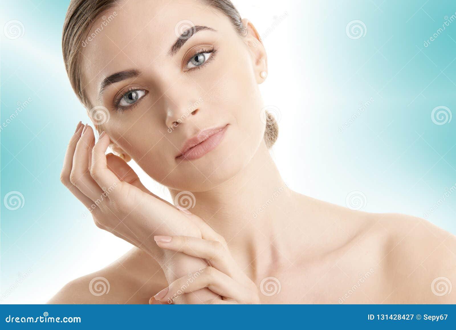 Ung kvinna med glödande hud som poserar på isolerat ljus - blå bakgrund