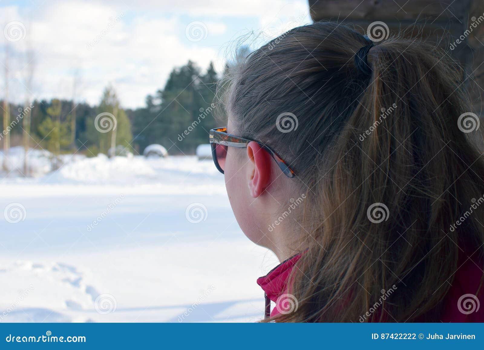 Ung kvinna med hållande ögonen på vinterlandskap för hästsvans på hennes egna tankar