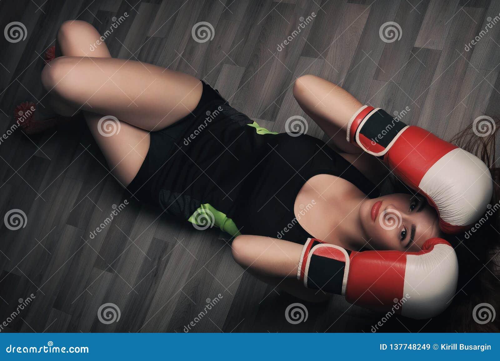 Ung kvinna med långt blont hår och stängda ögon, iklädda konditionkläder och bärande röda boxas handskar som ligger på mörkt golv